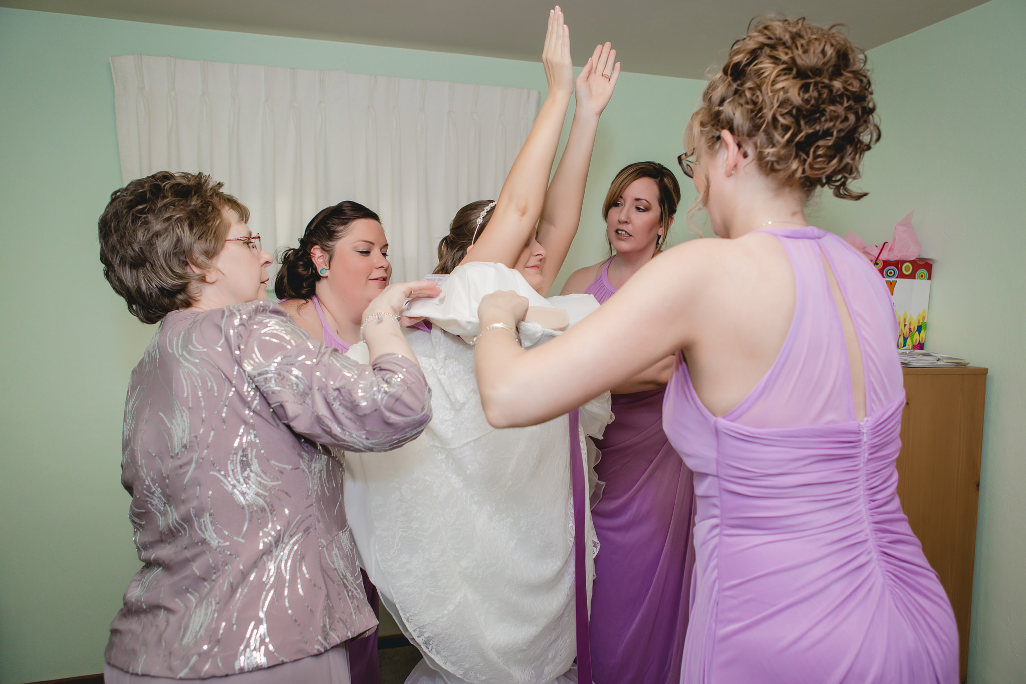 Mother of the bride and bridesmaids helping the bride into her wedding dress