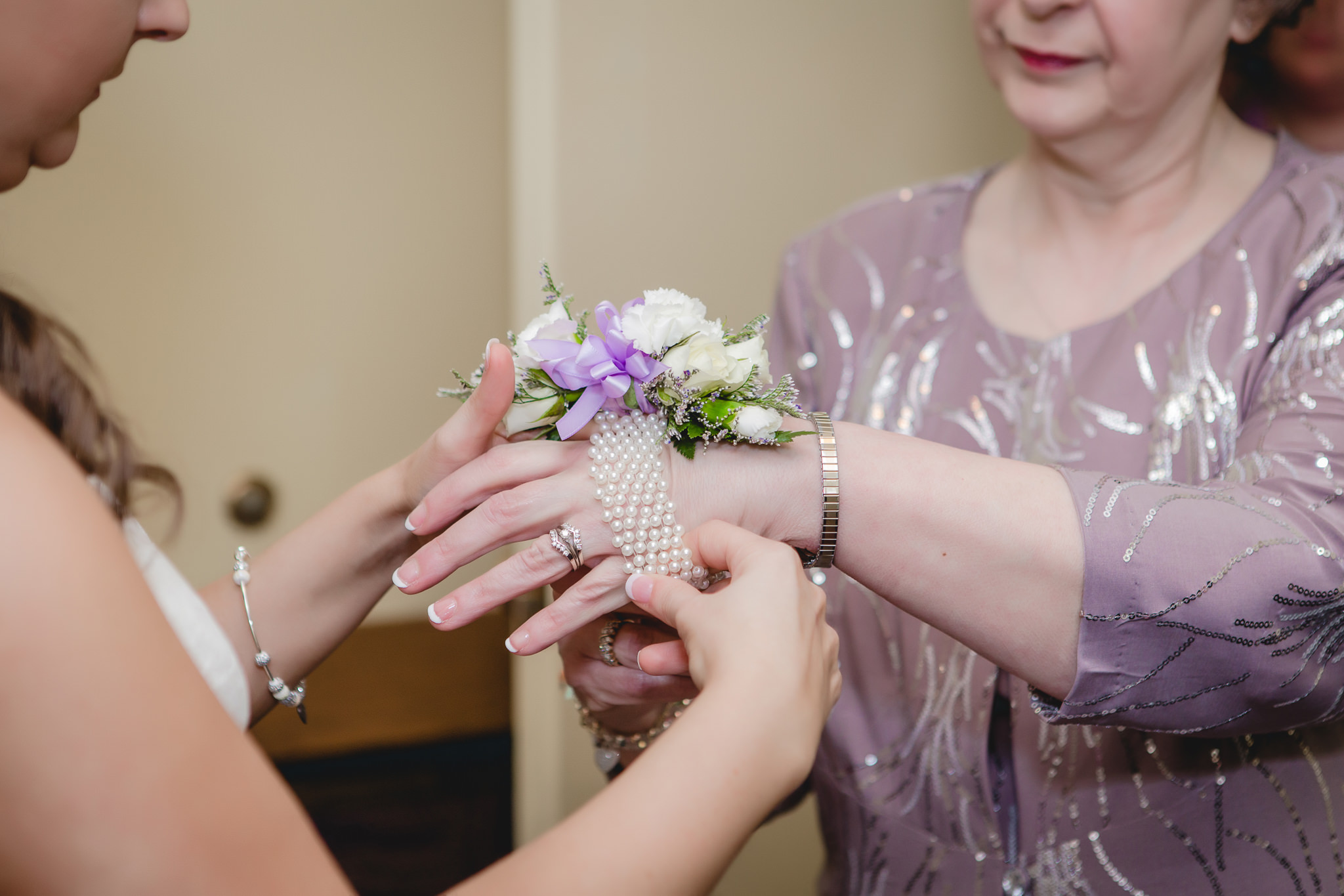 Bride puts wrist corsage on her mother's wrist