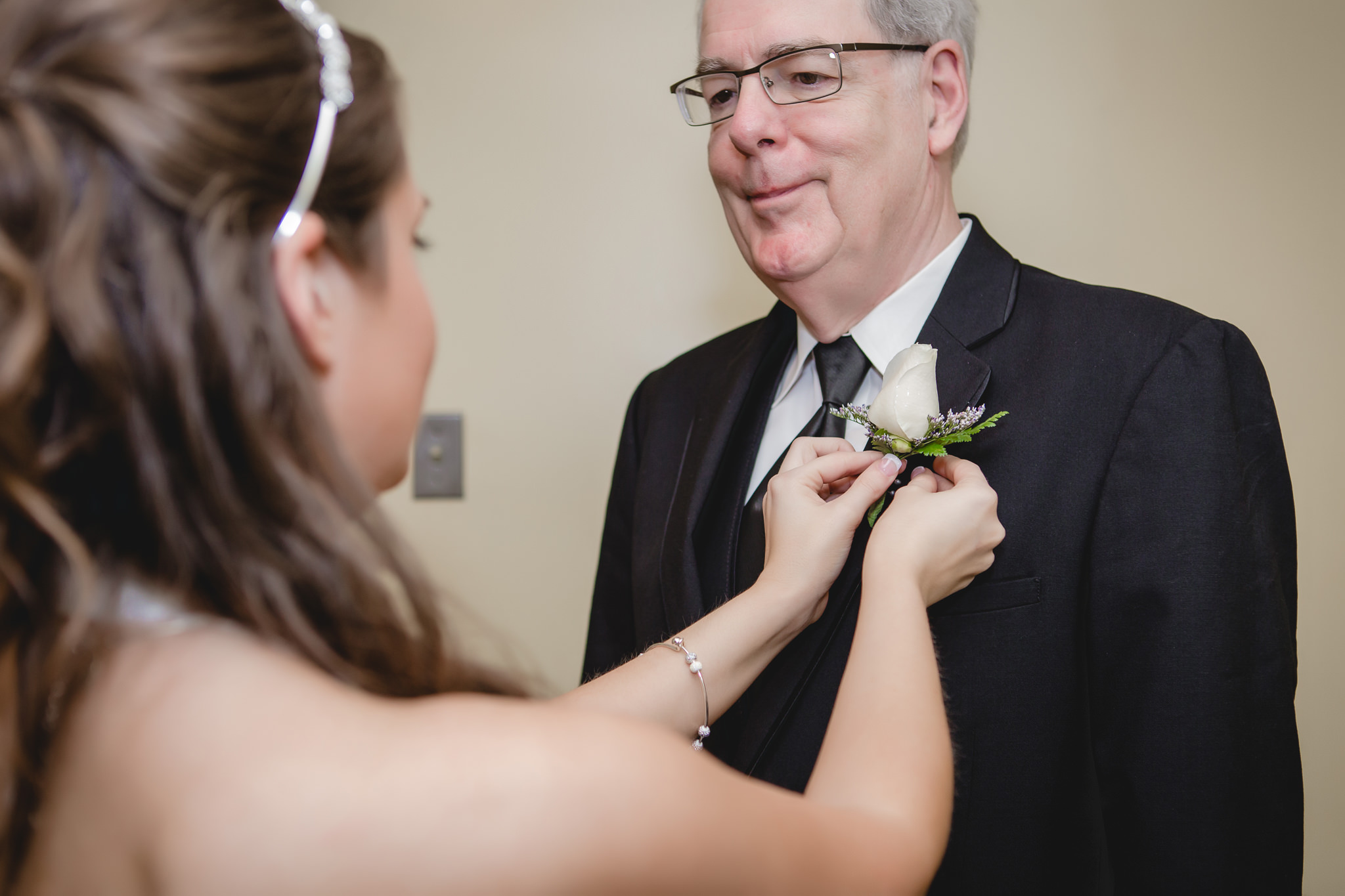 Bride pins boutonniere on her father's lapel before her wedding ceremony