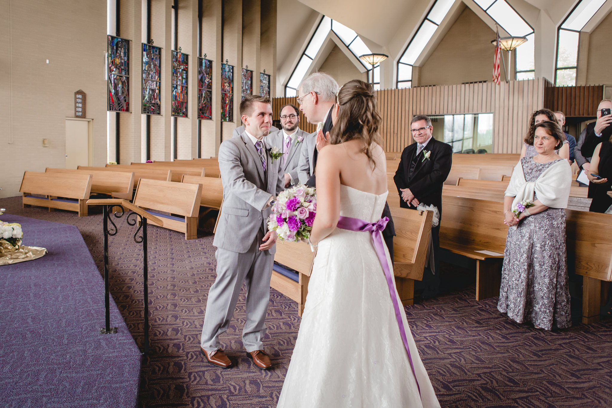 Groom shakes father-in-law's hand at St. Malachy Catholic Church