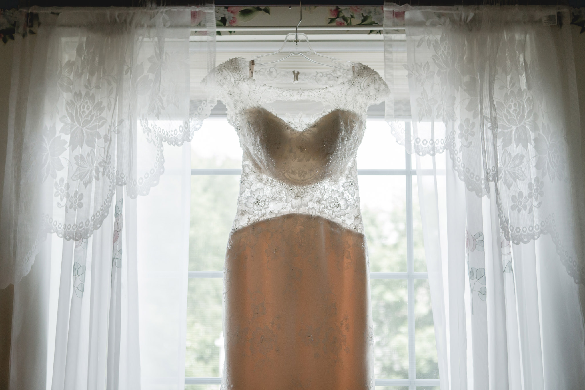Bride's Maggie Sottero gown hangs in the window at Greystone Fields