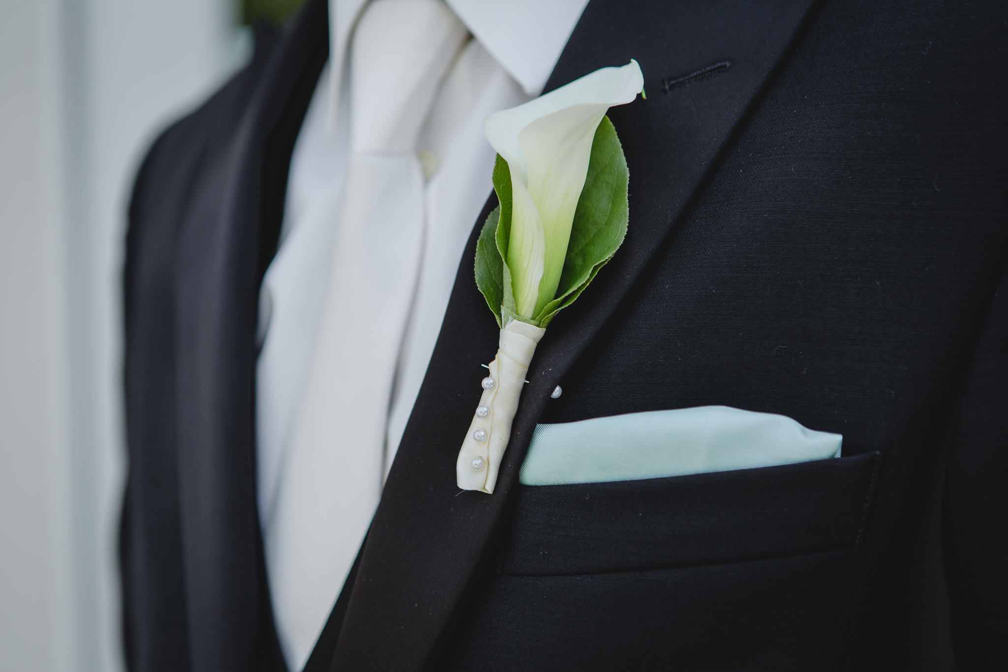 Closeup of groom's boutonniere and pocket square