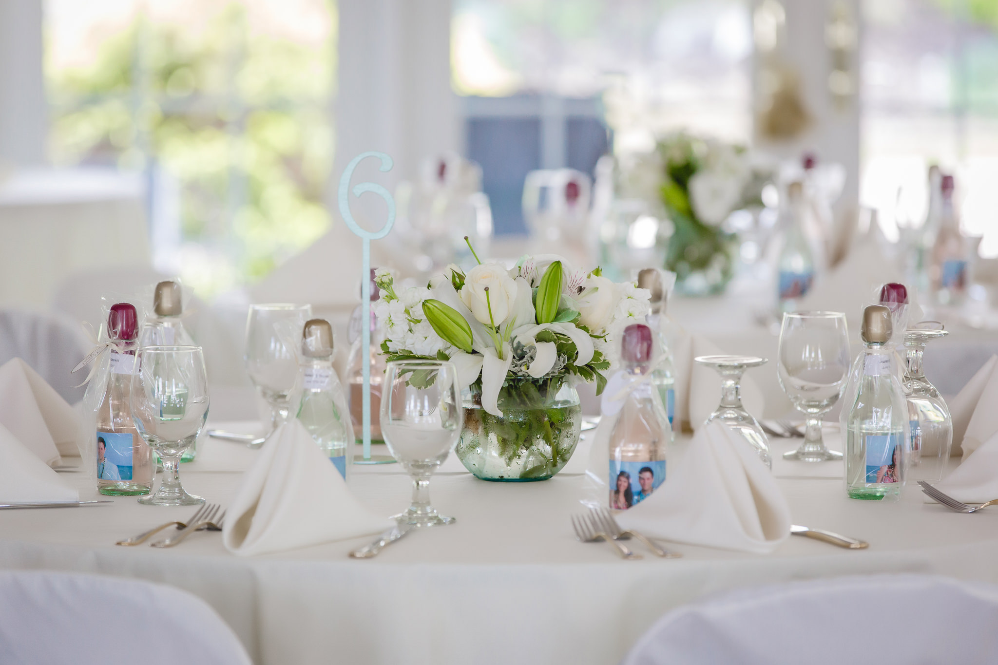 Centerpieces and teal table numbers at a wedding reception at Greystone Fields