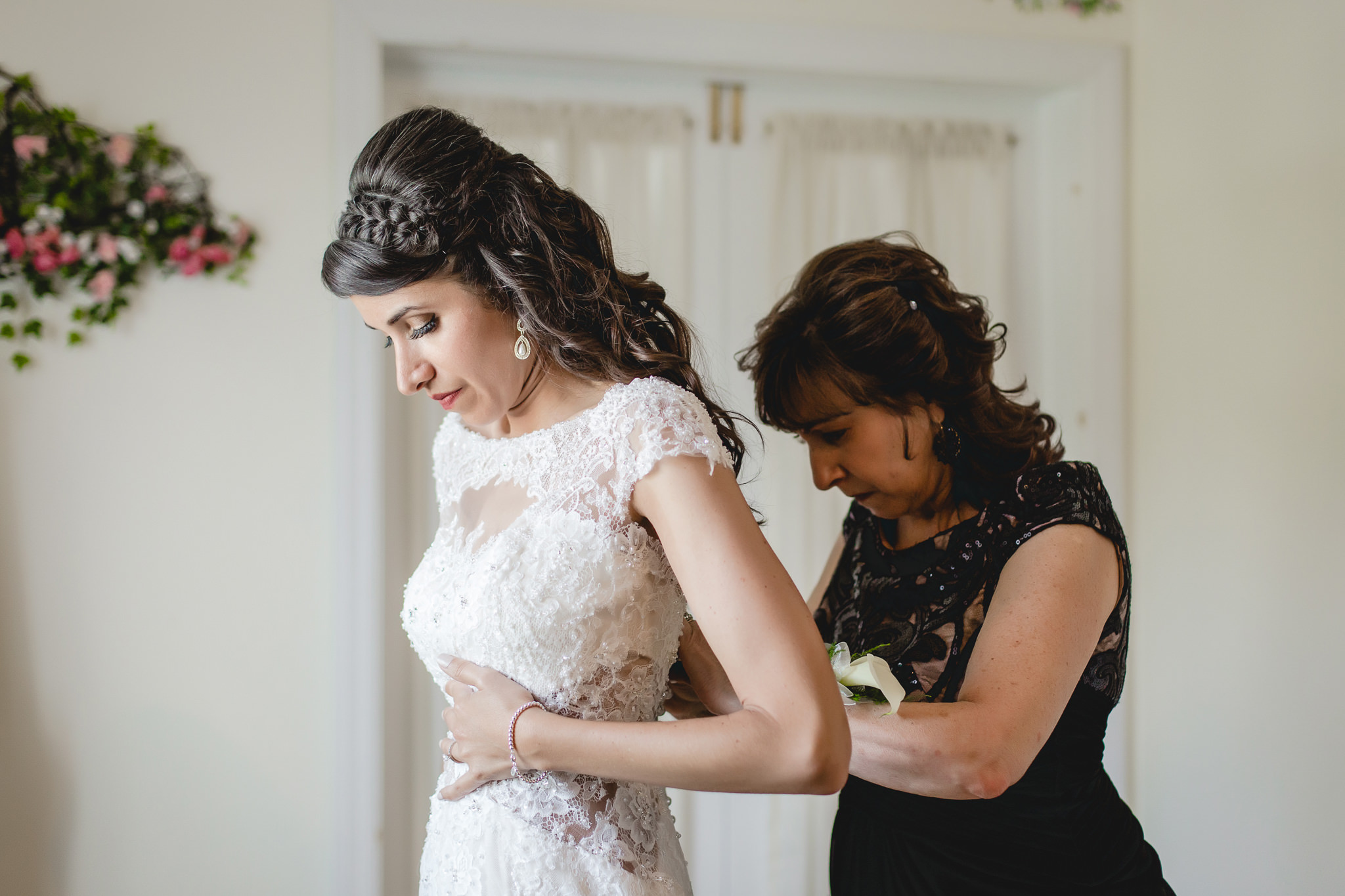Mother of the bride helps the bride get into her dress at Greystone Fields