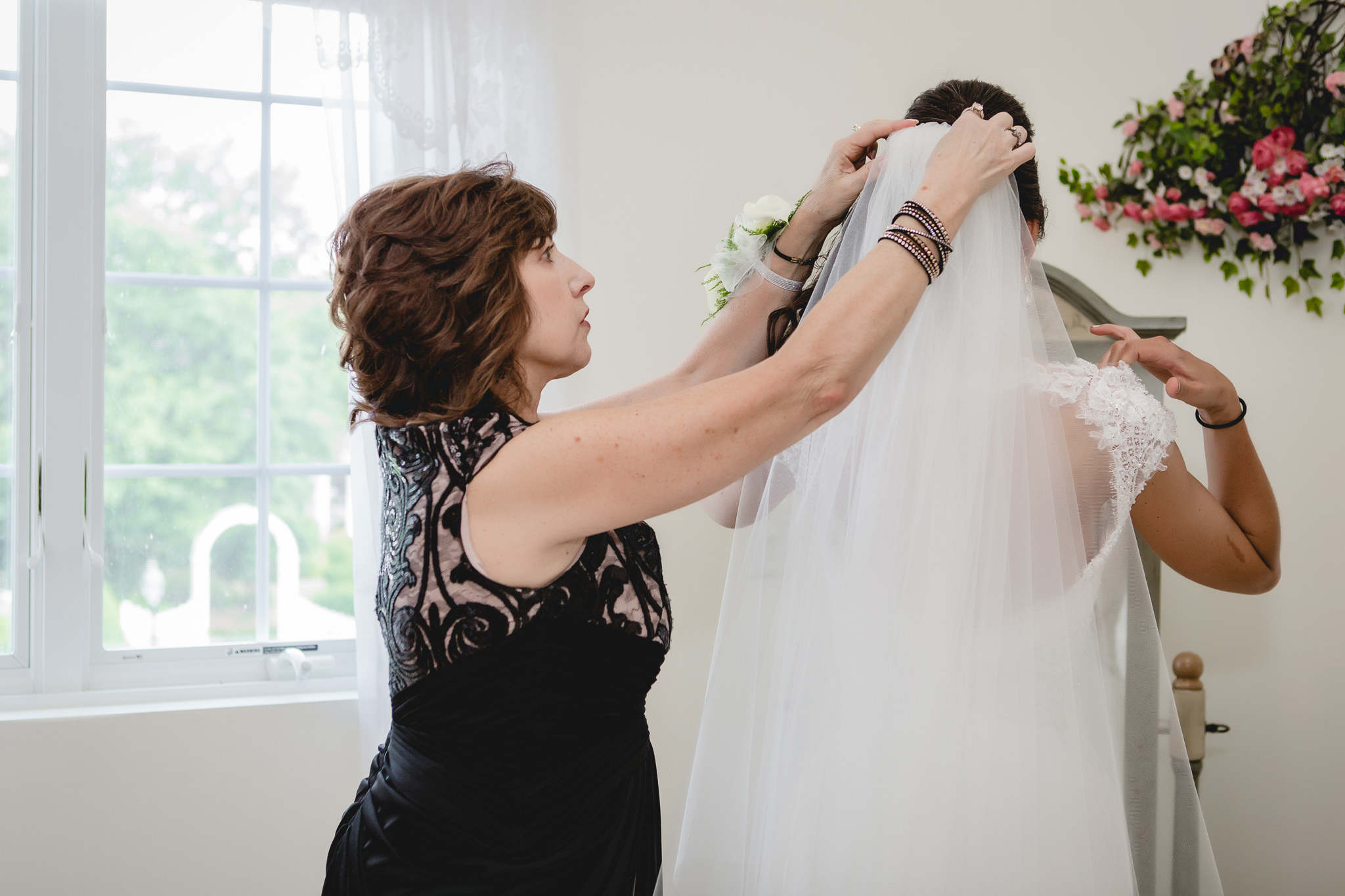 Mother of the bride puts the veil into the bride's hair