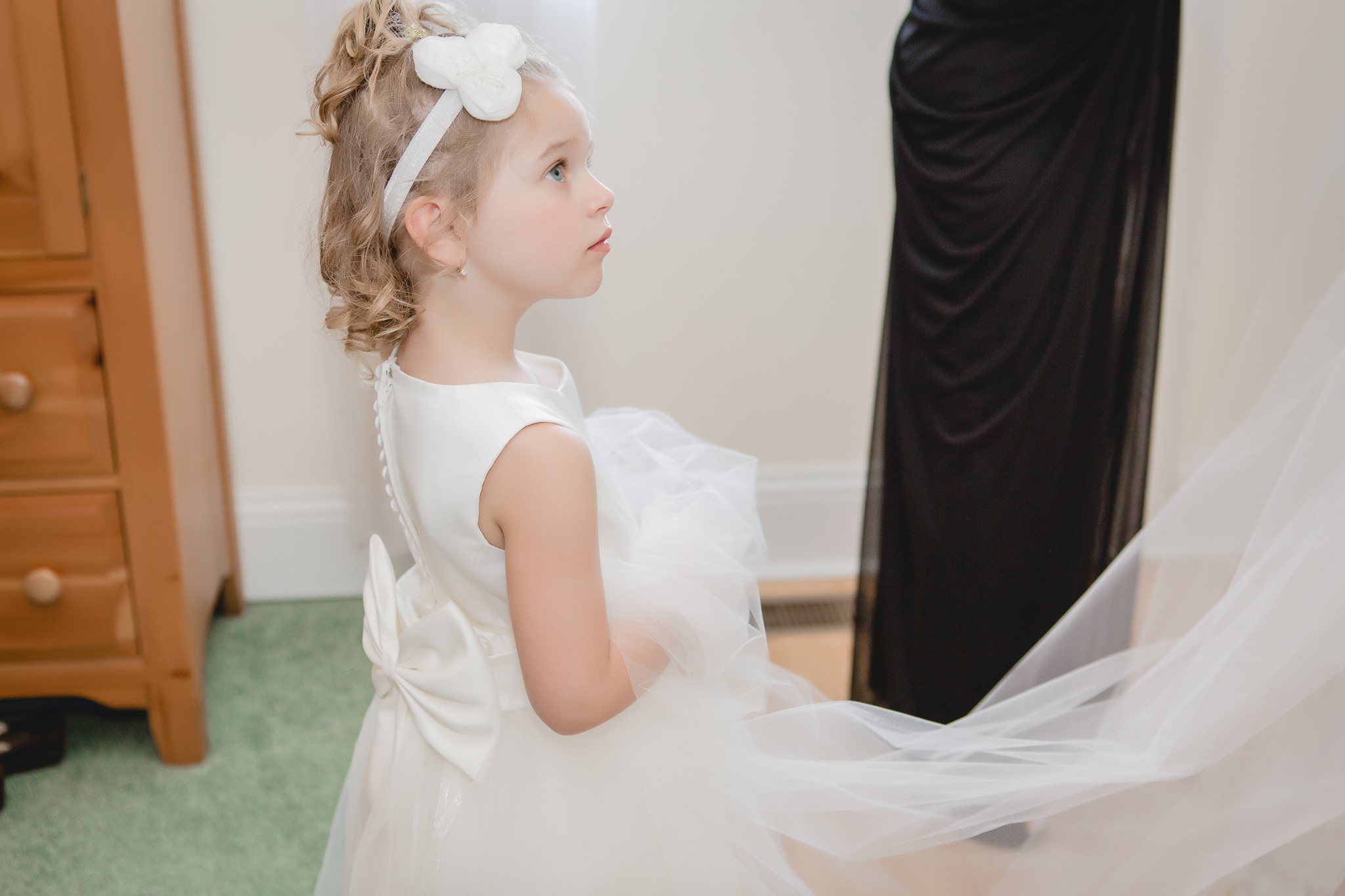 Flower girl holds bride's veil as she gets into her dress