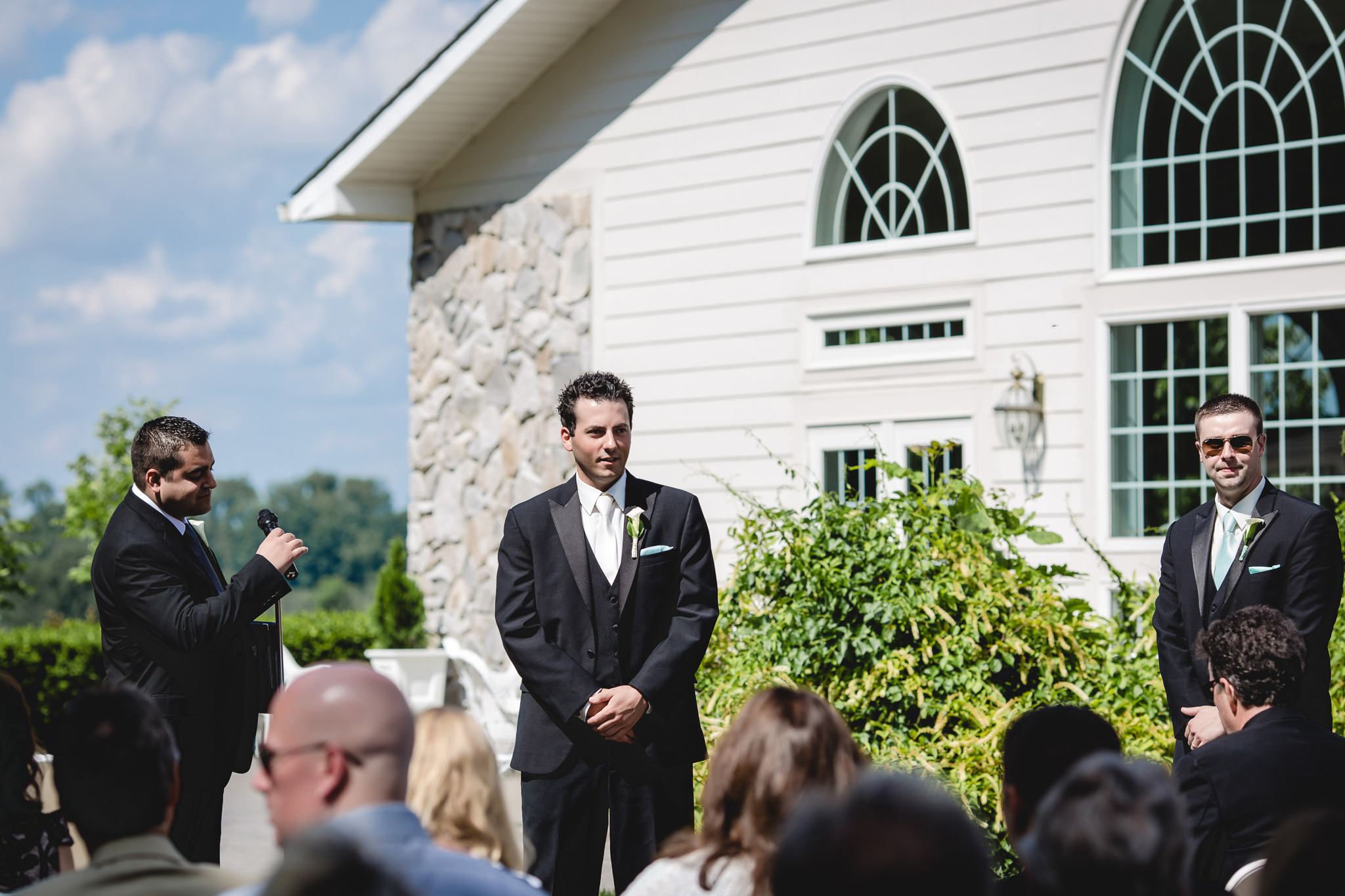 Groom watches his bride walking down the aisle at a wedding ceremony at Greystone Fields