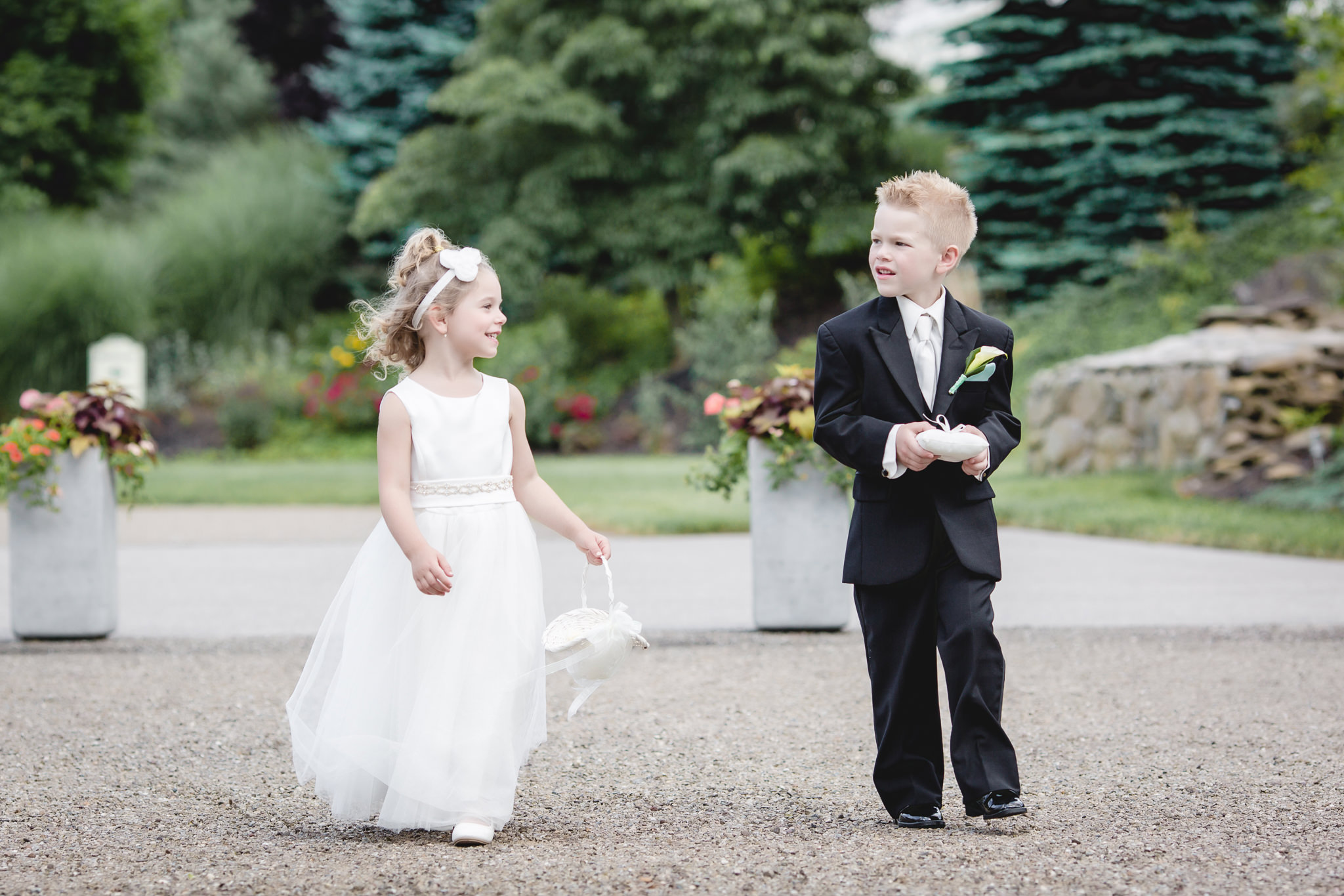 Flower girl and ring bearer walking down the aisle at Greystone Fields