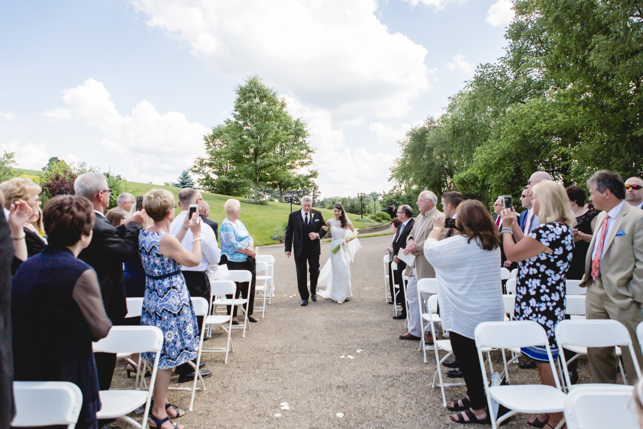 Bride walks down the aisle with her father at an outdoor wedding ceremony at Greystone Fields
