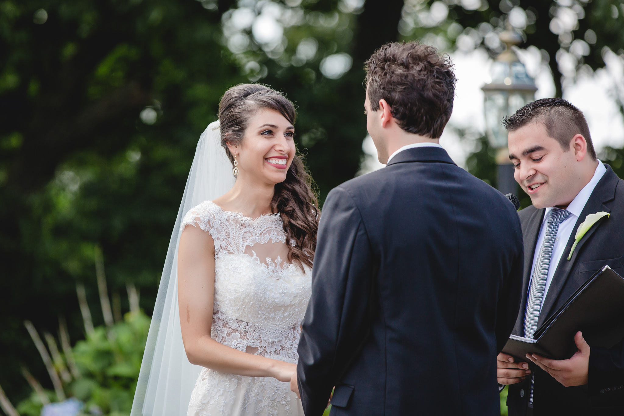 Bride smiles at her groom during their outdoor wedding ceremony