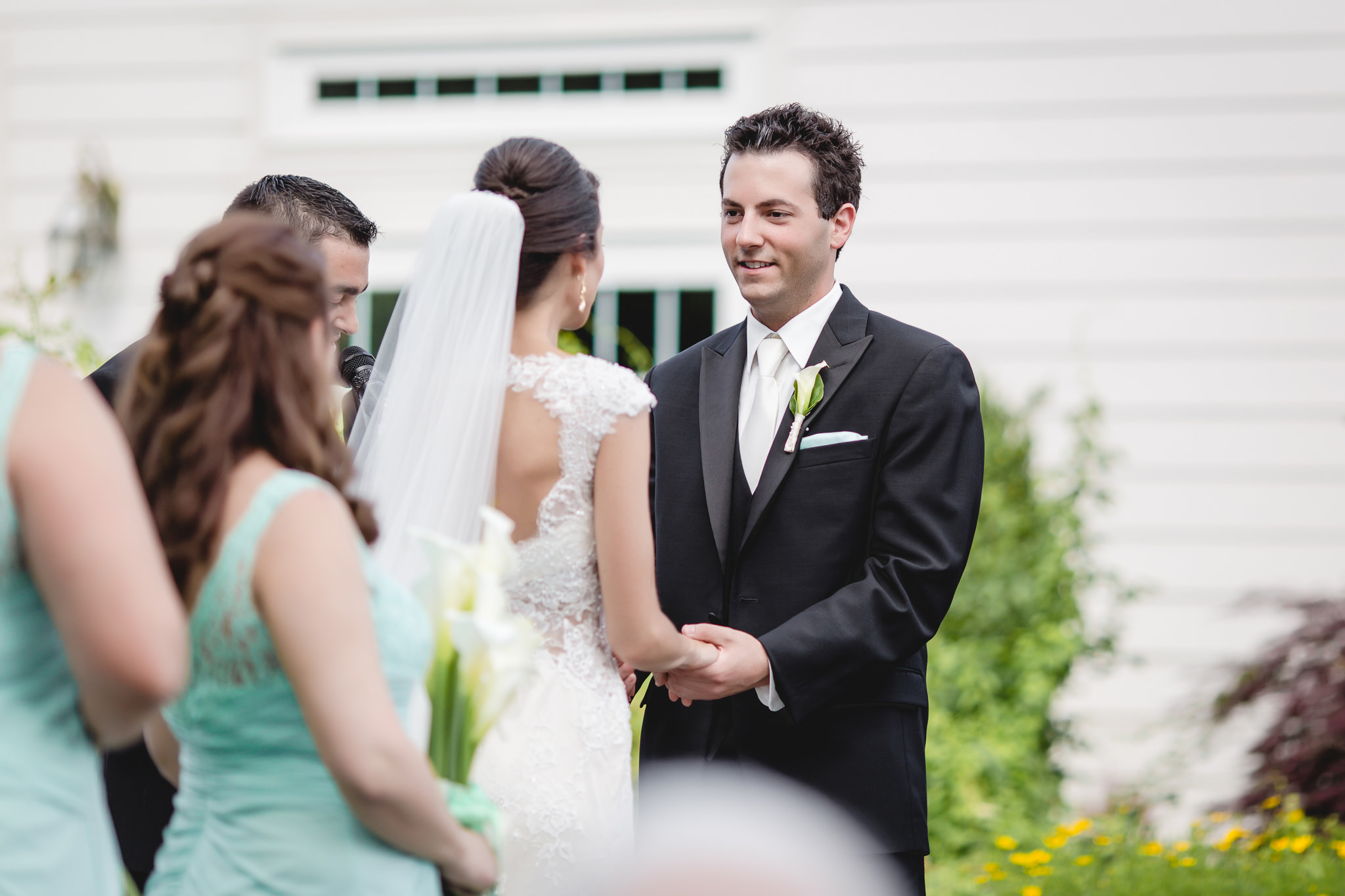 Groom smiles at his bride at their Greystone Fields wedding ceremony