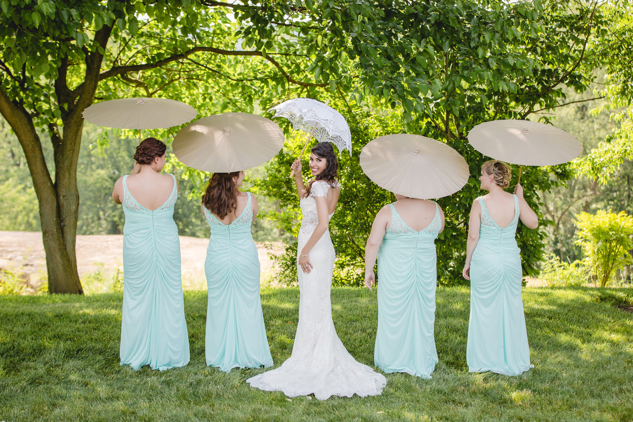 Bride and her bridesmaids posing with umbrellas at Greystone Fields