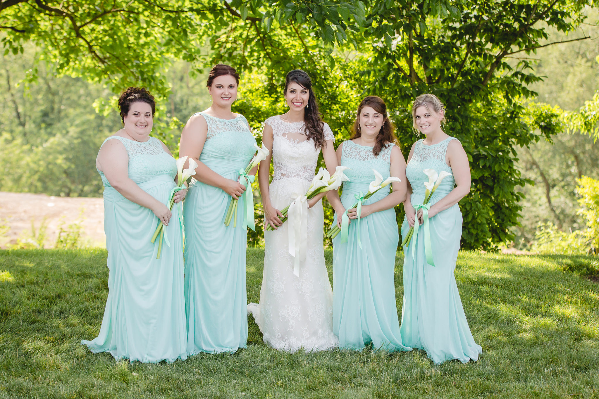 Bridesmaids in teal dresses holding calla lilies