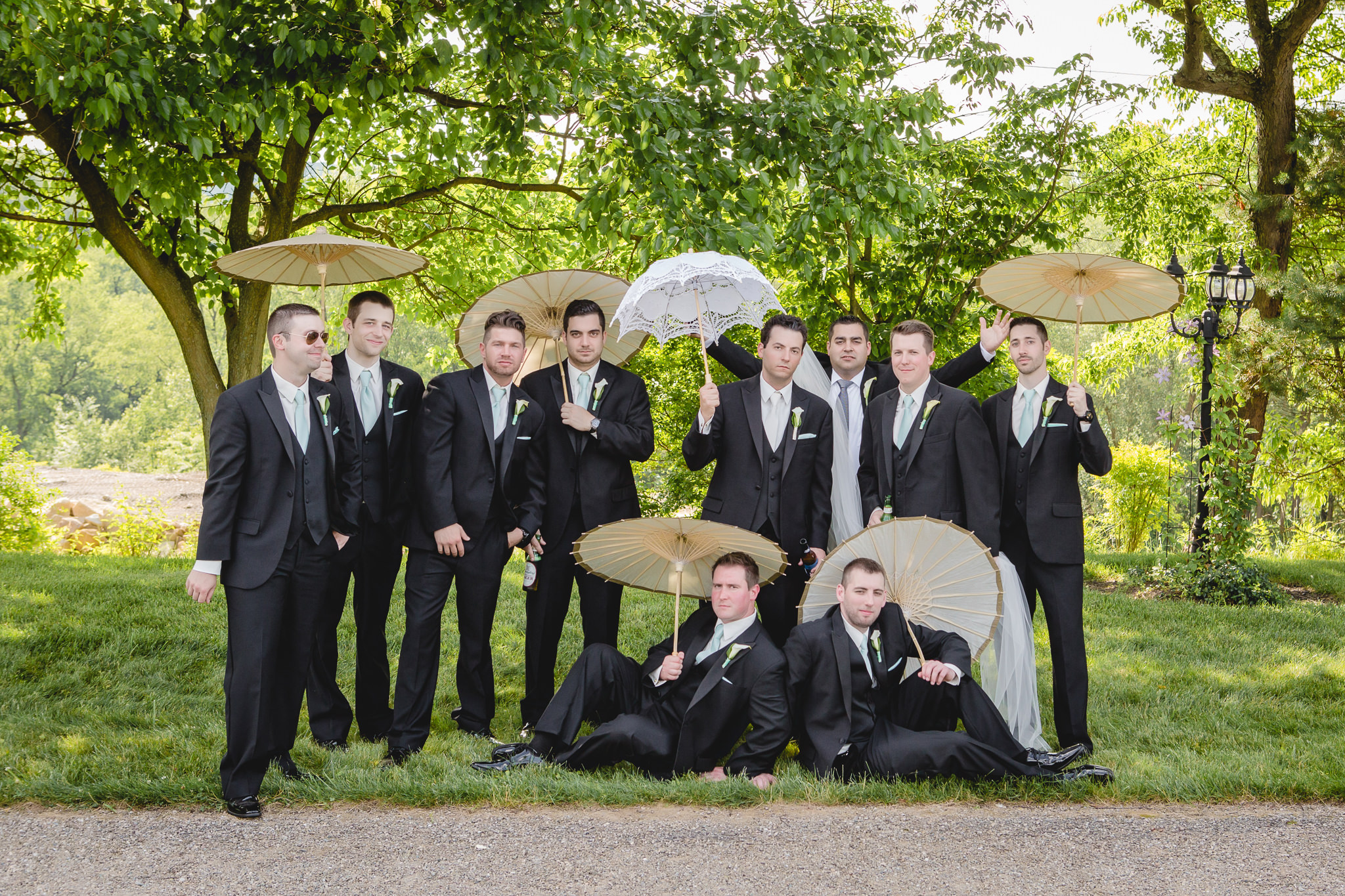 Groomsmen pose with bride's veil and umbrellas at Greystone Fields