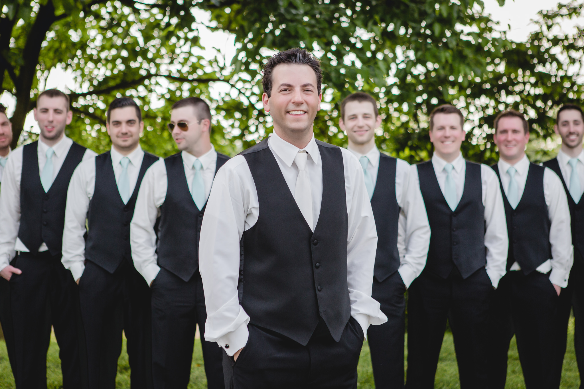 Groom poses with his groomsmen at his June wedding