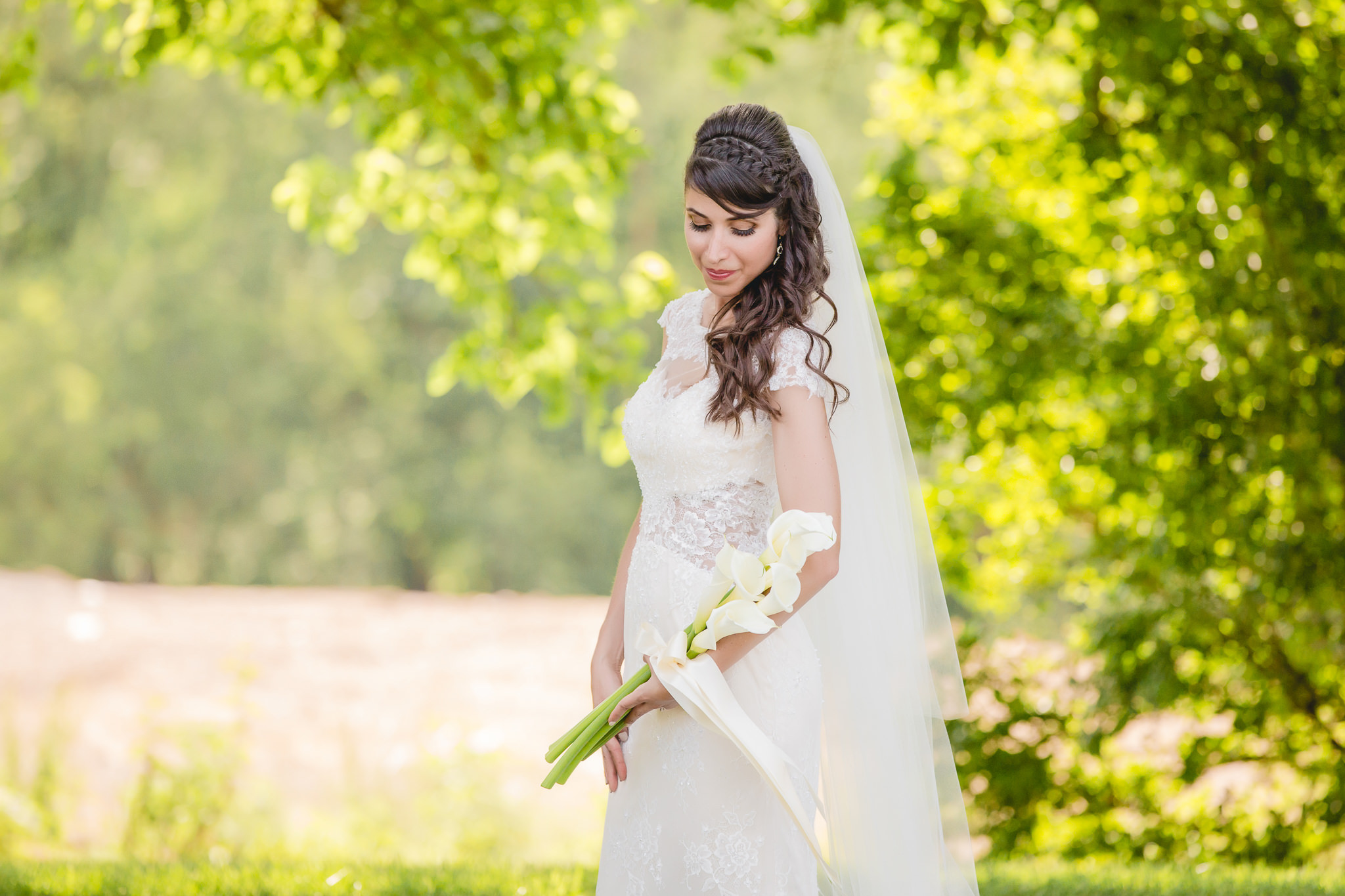 Bride poses with her bouquet of calla lilies
