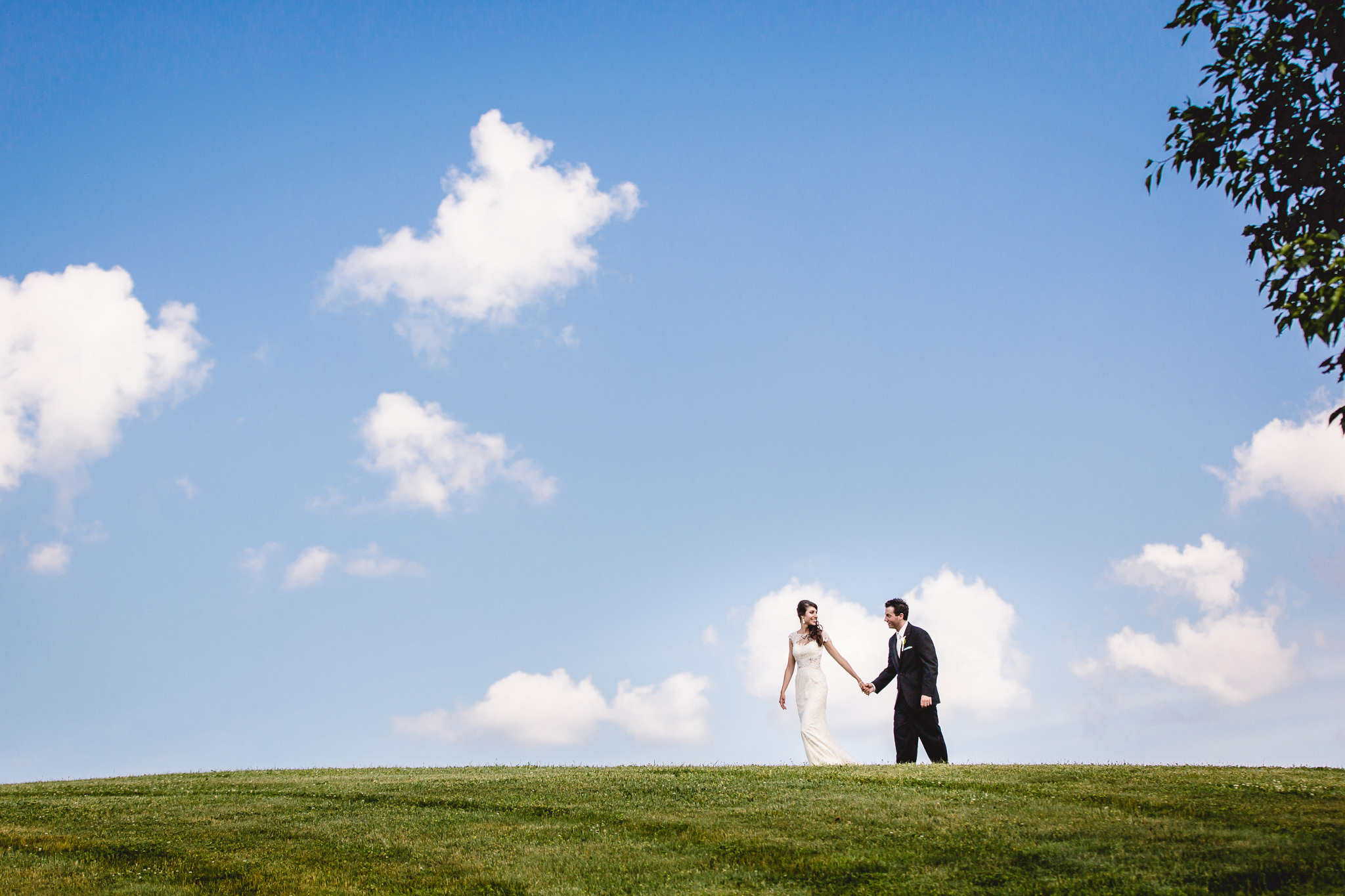 Bride and groom walk hand in hand on top of a hill at Greystone Fields