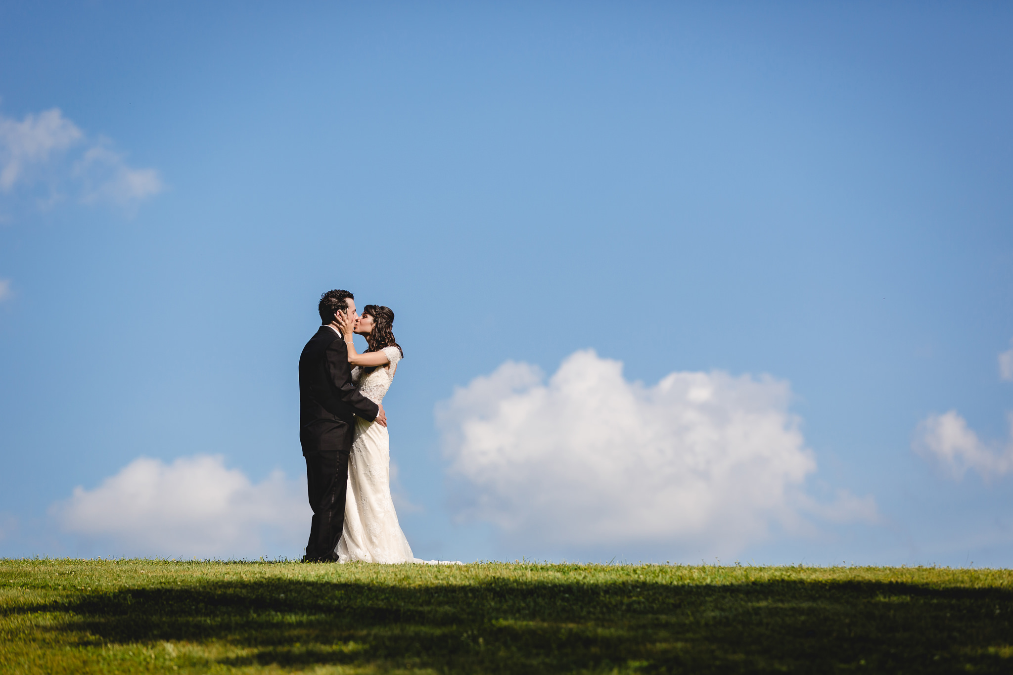 Bride and groom kiss in front of blue skies on a hill at Greystone Fields