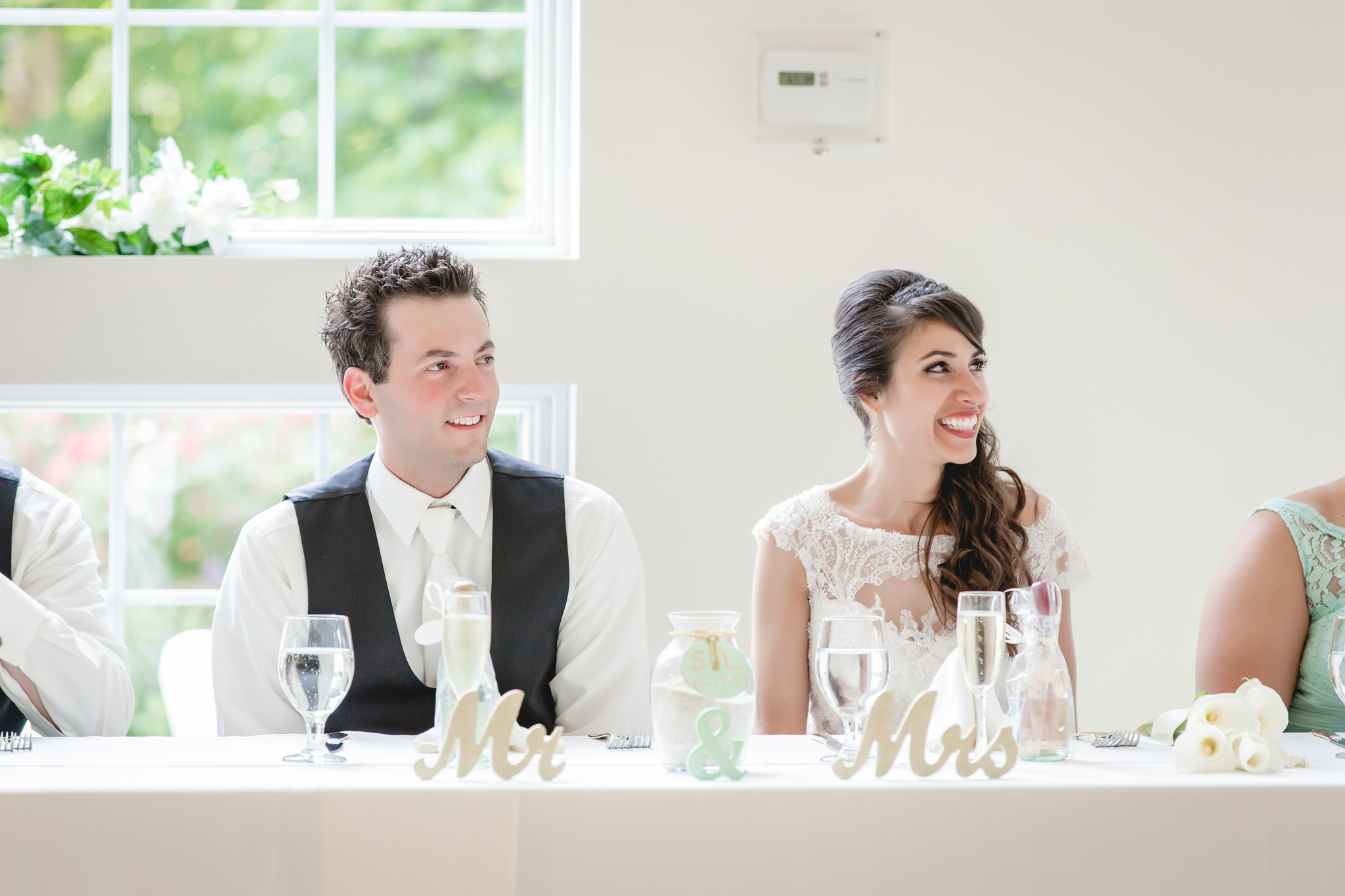 Bride and groom laugh during speeches at Greystone Fields