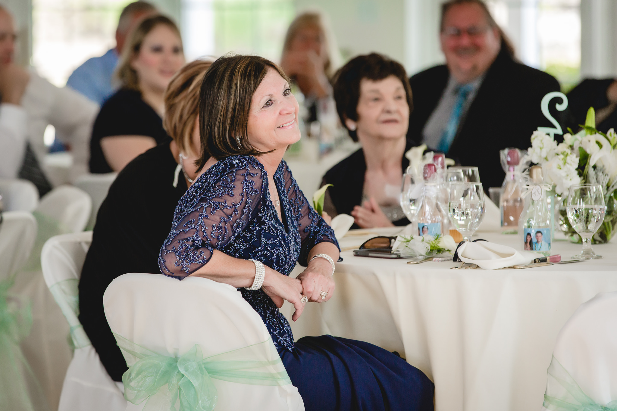 Mother of the groom smiles during speeches at Greystone Fields