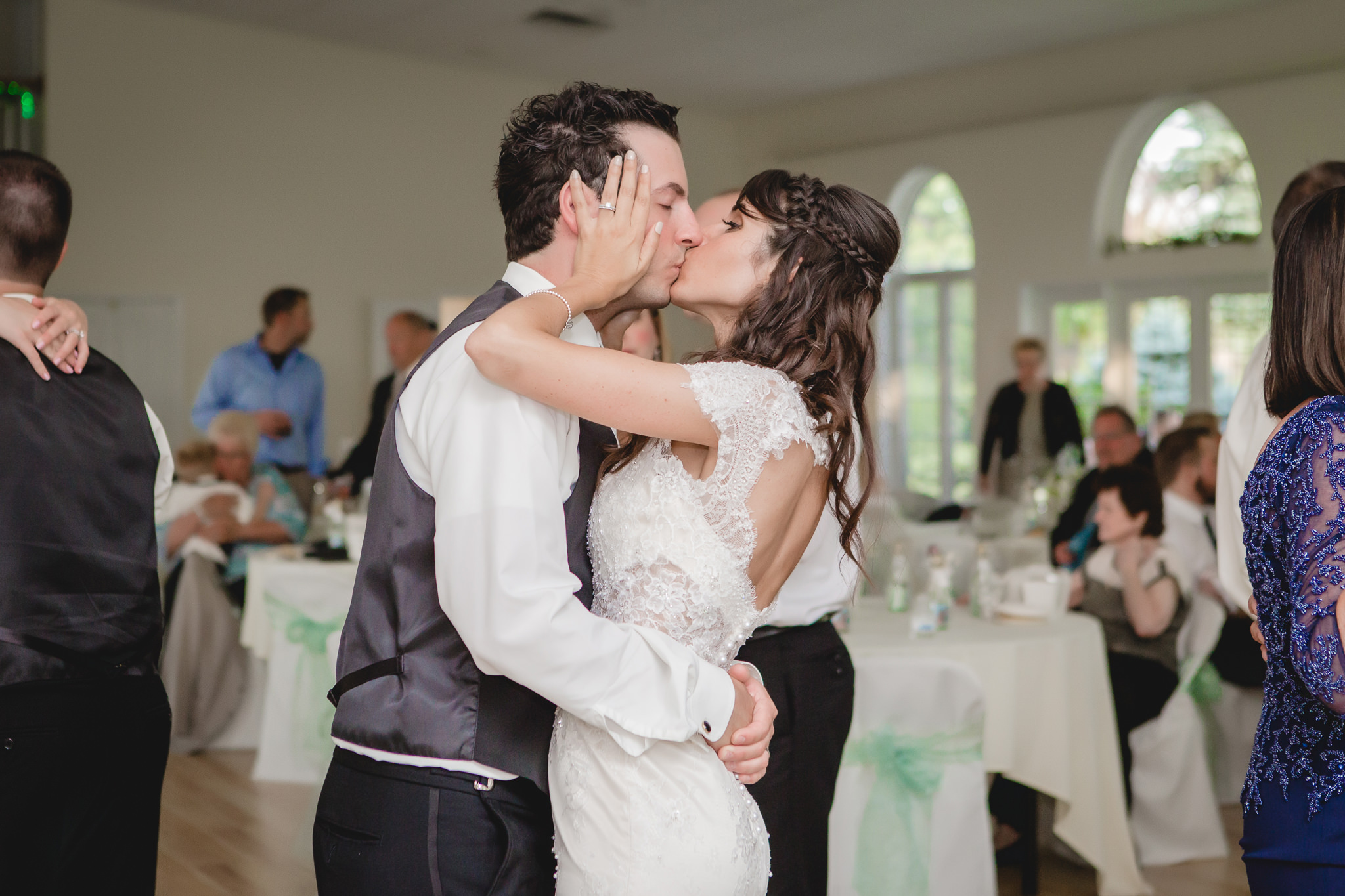 Bride and groom kiss on the dance floor at their wedding reception