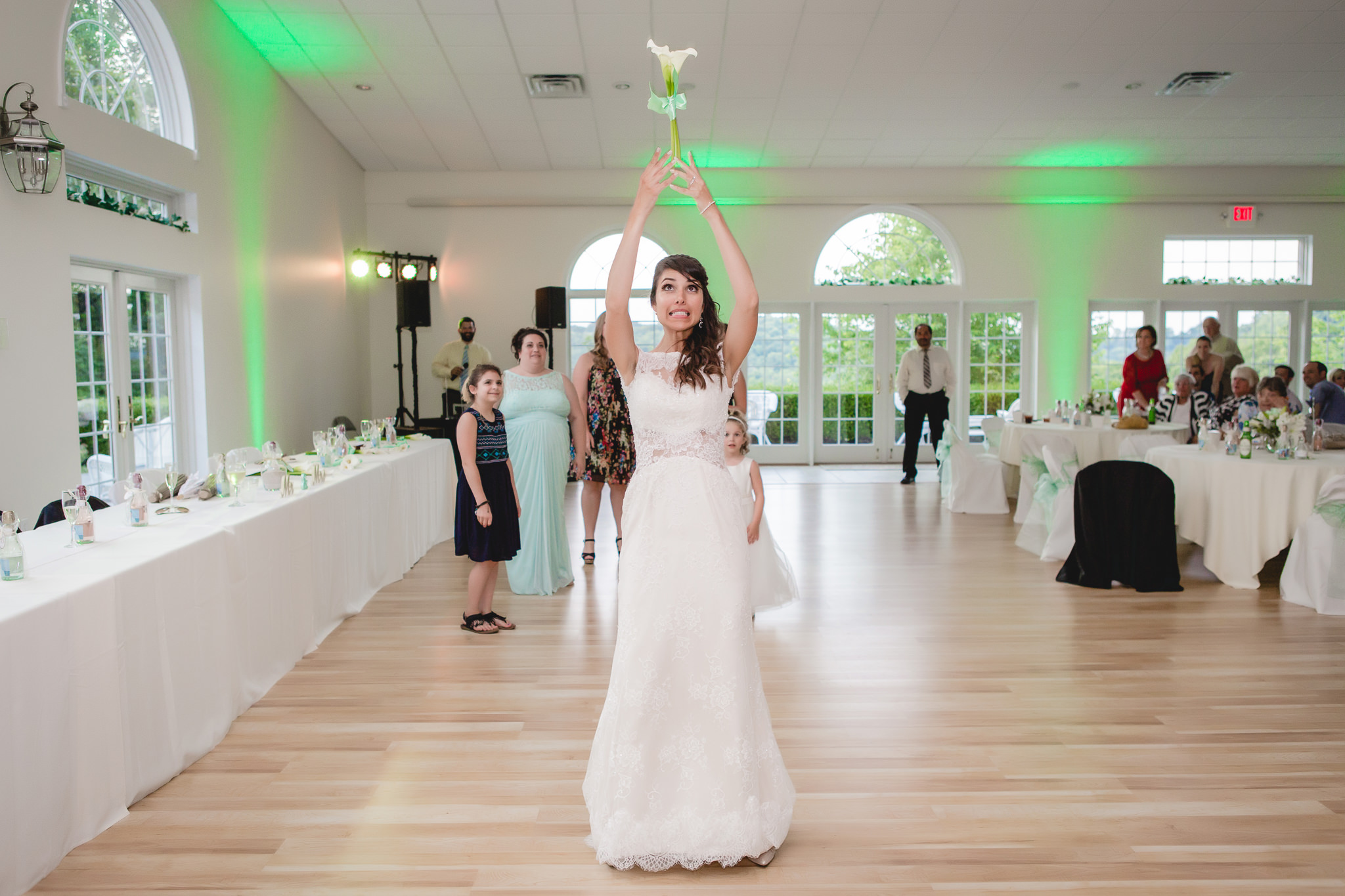Bride tosses her bouquet to single ladies at her wedding reception