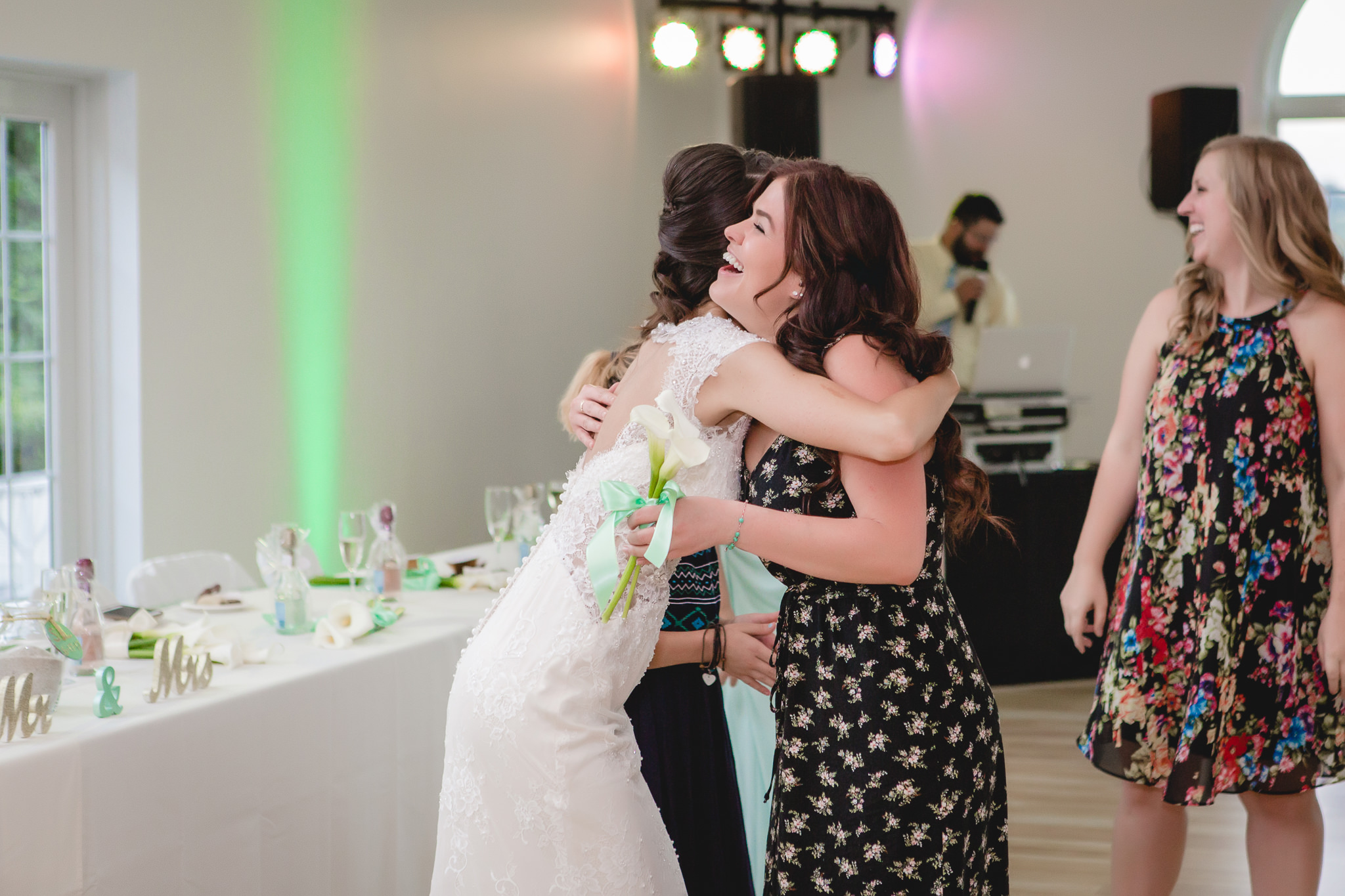 Bride hugs the single lady who caught the bouquet