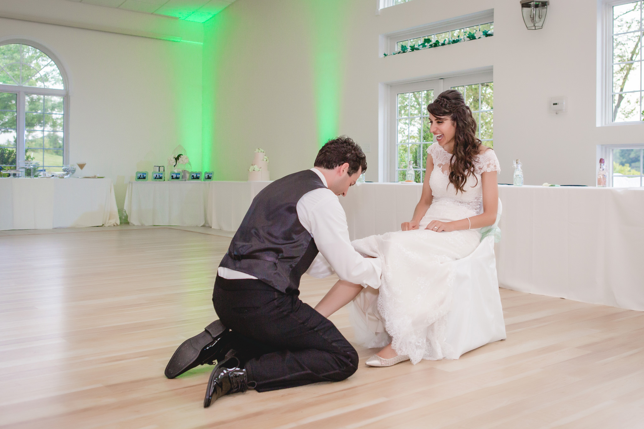 Groom removes the bride's garter at Greystone Fields