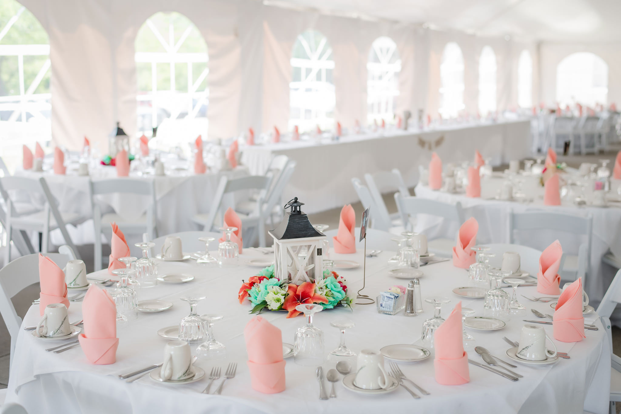 Tables decorated for a wedding reception inside a tent at Linden Hall