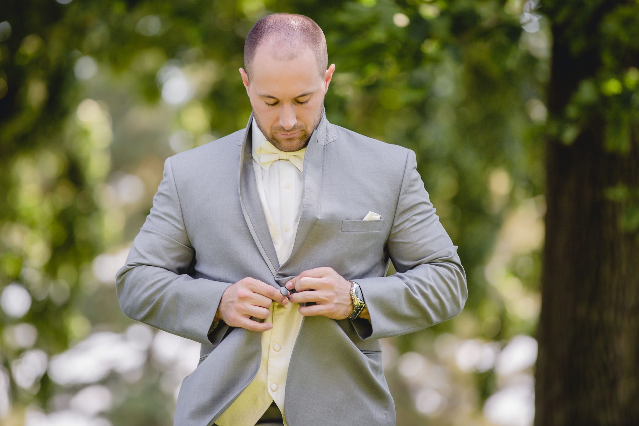 Groom buttoning his tuxedo jacket