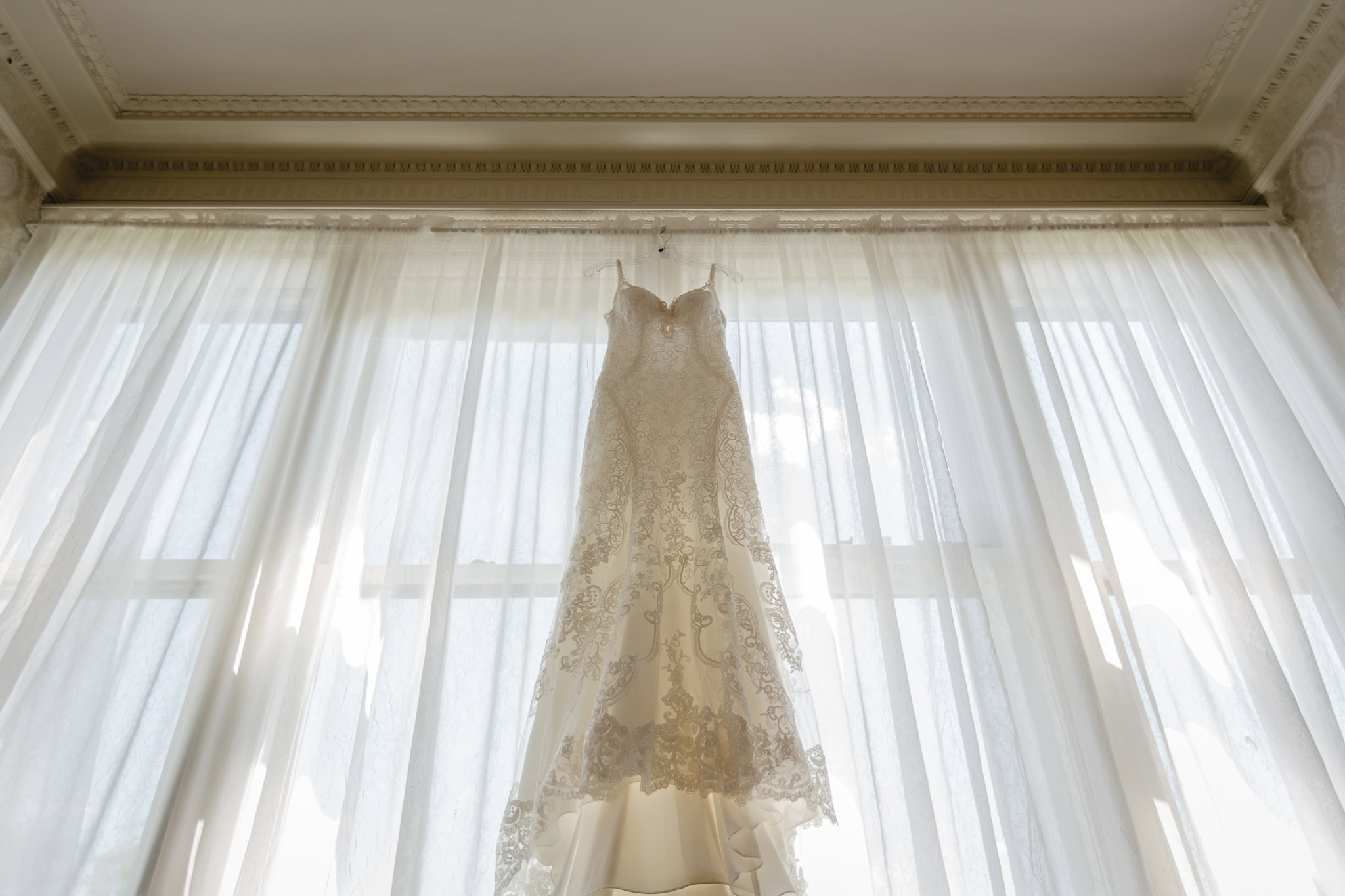 Bride's lace dress hanging in a window inside Linden Hall mansion