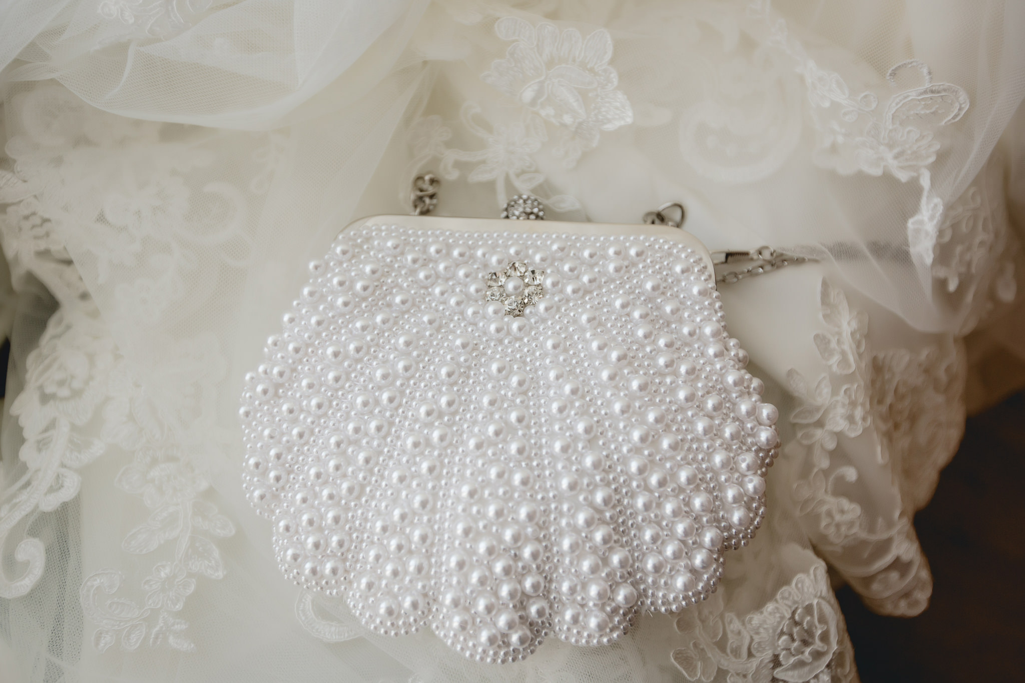 Brides white pearl purse sitting on her wedding dress train