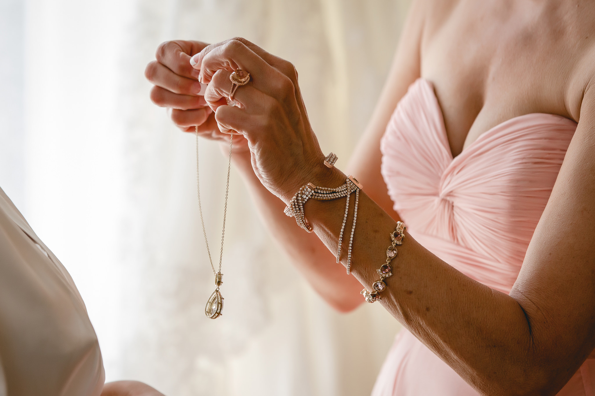 Mother of the bride holding bride's necklace