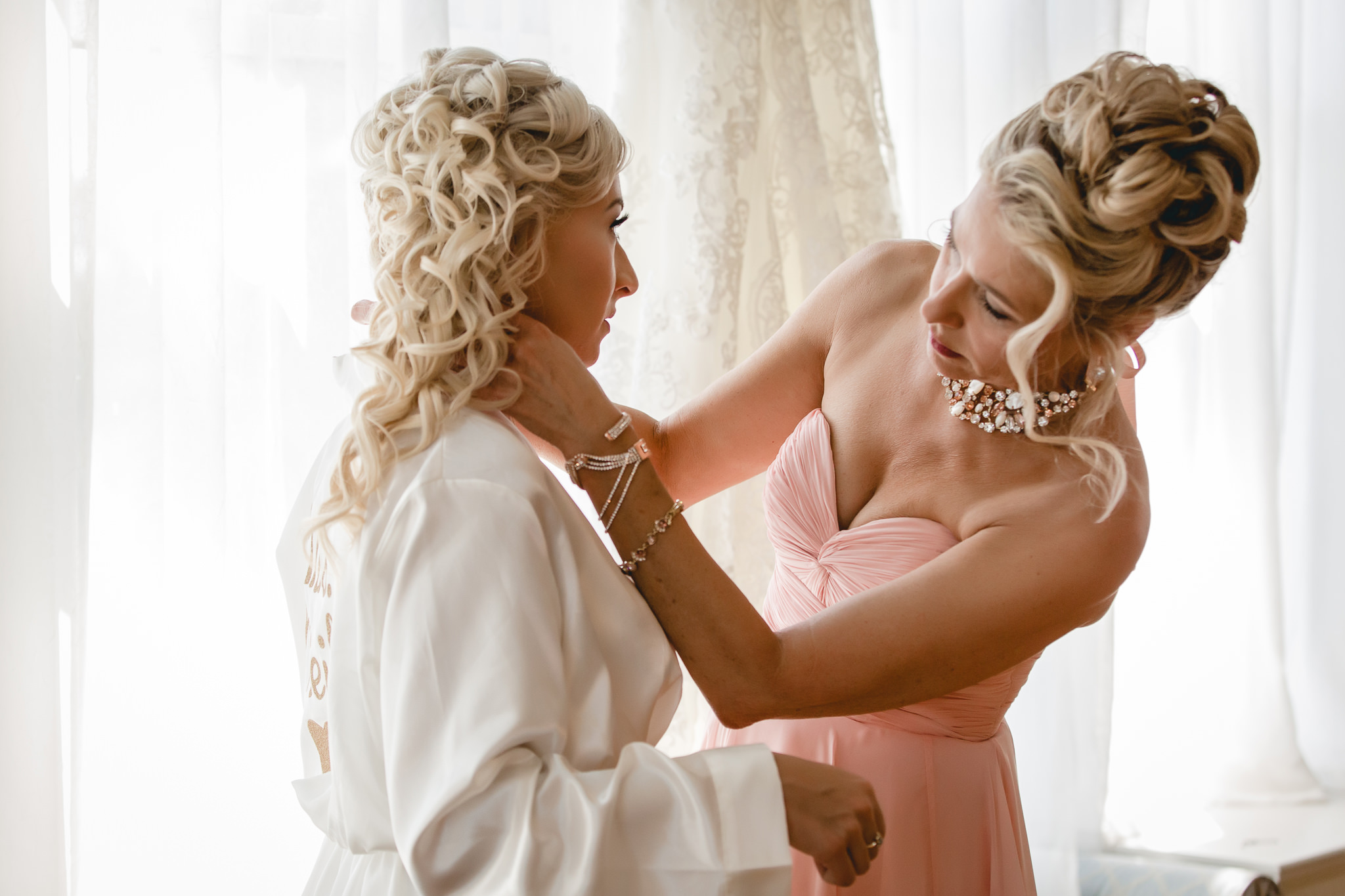 Mother of the bride puts bride's necklace on her