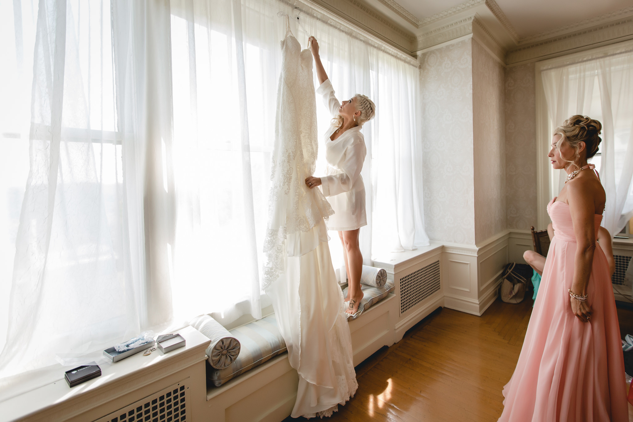 Bride taking her lace wedding dress off of the hanger