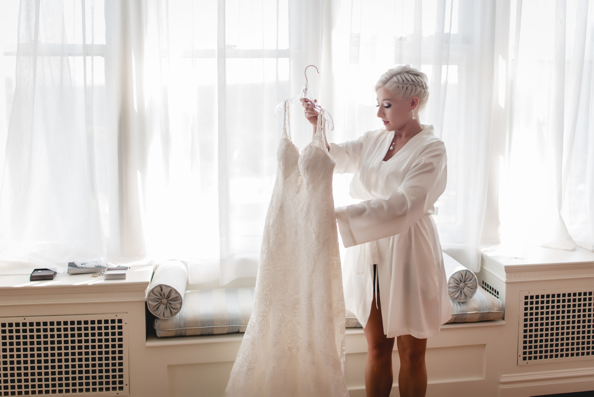 Bride getting her wedding dress ready to put on