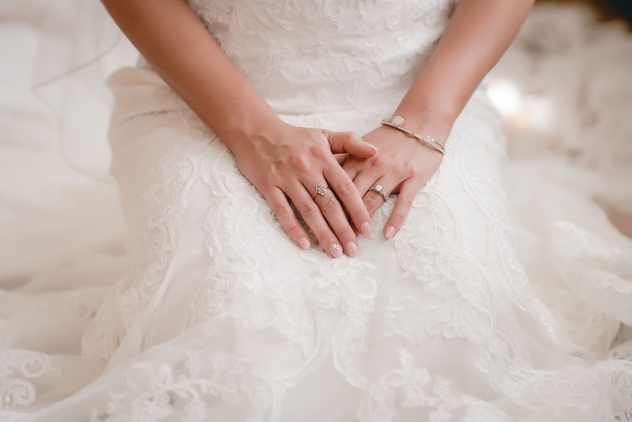 Closeup of bride's hands resting on her wedding dress