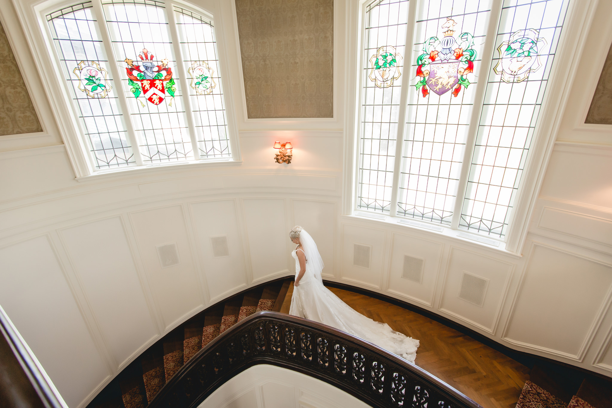 Bride walks down a grand staircase inside Linden Hall mansion