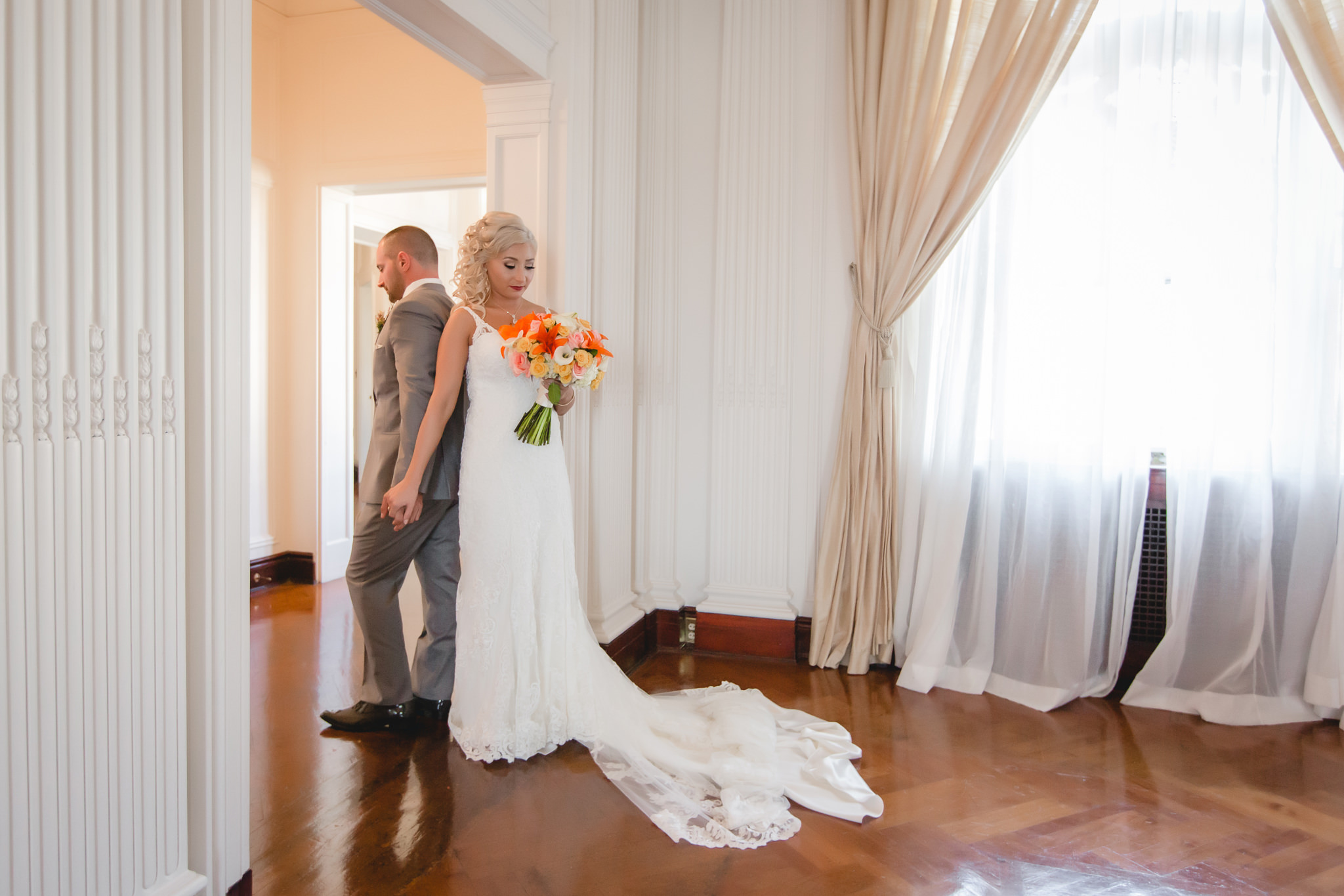 Bride and groom do a first touch around a doorway before their ceremony