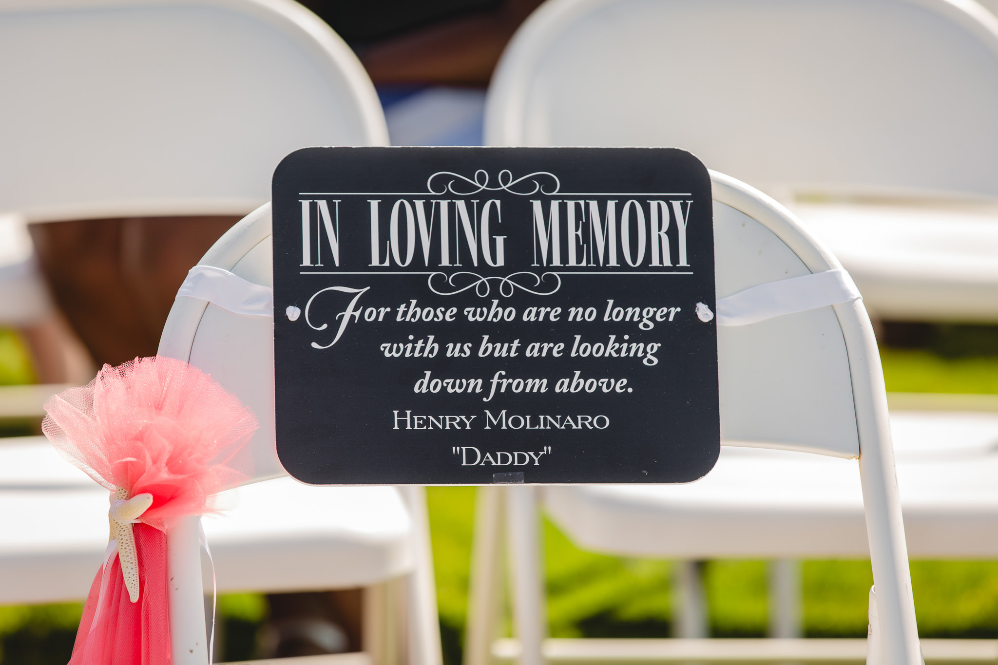 A memorial sign for the bride's father at her wedding ceremony