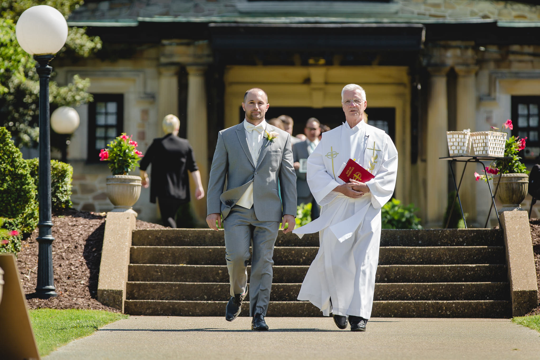 Groom and priest walk down the aisle at an outdoor wedding ceremony
