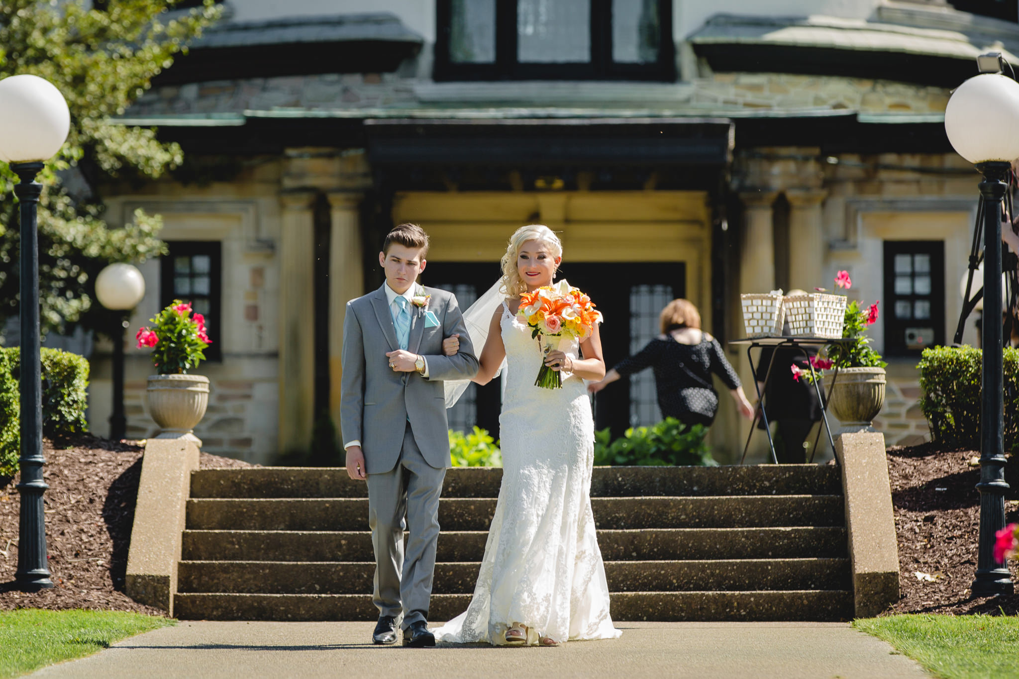 Bride's brother walks her down the aisle at an outdoor ceremony at Linden Hall