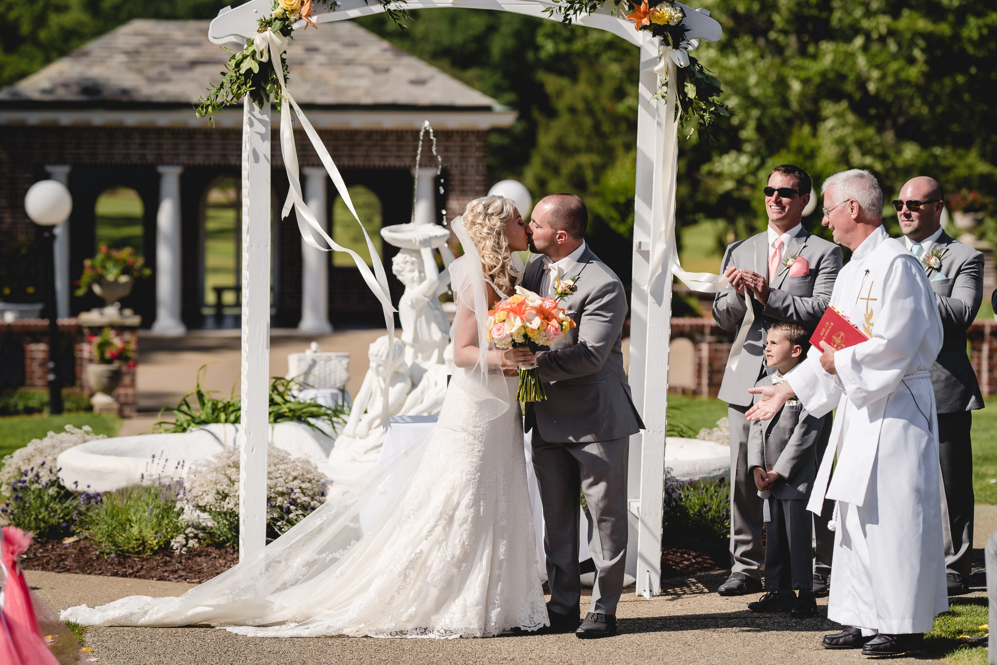Bride and groom share their first kiss at an outdoor wedding ceremony