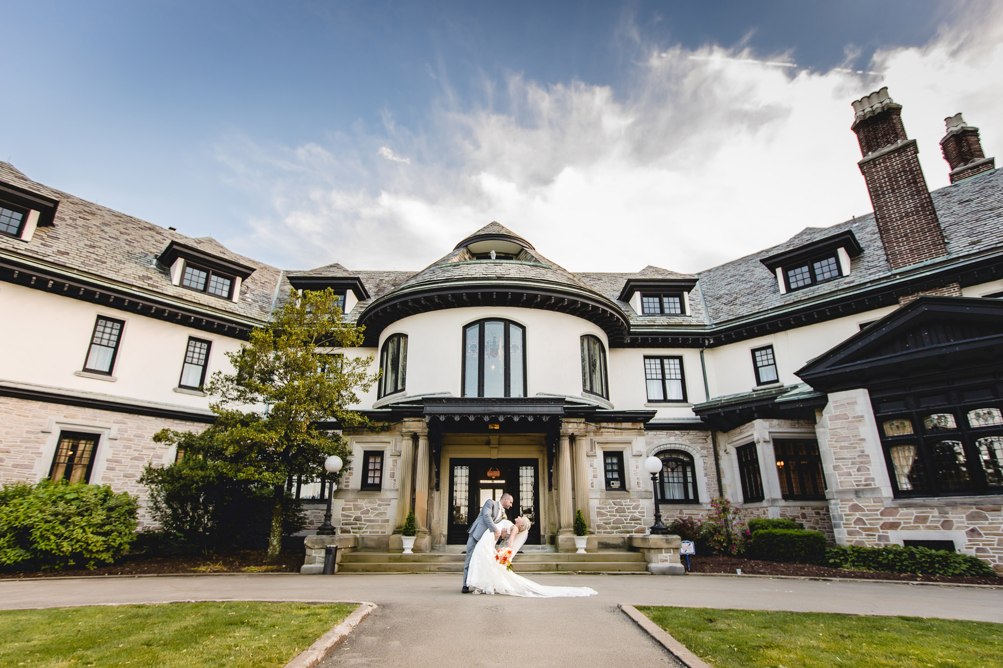 Groom dips his bride in front of Linden Hall mansion