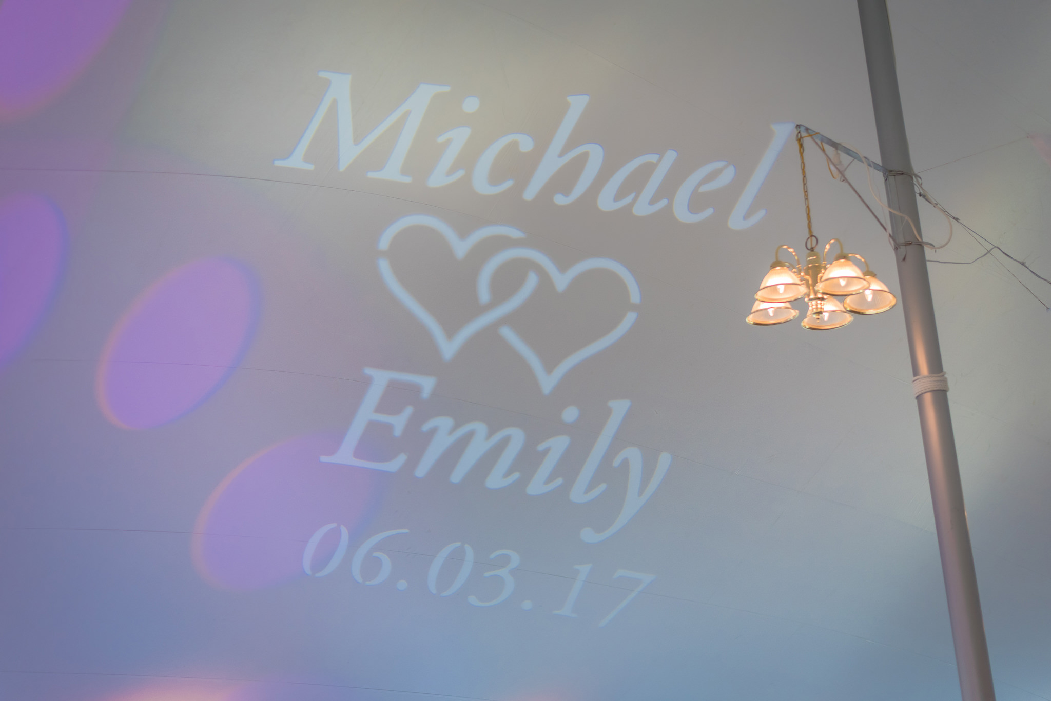 Monogram displayed on the tent ceiling during a wedding reception