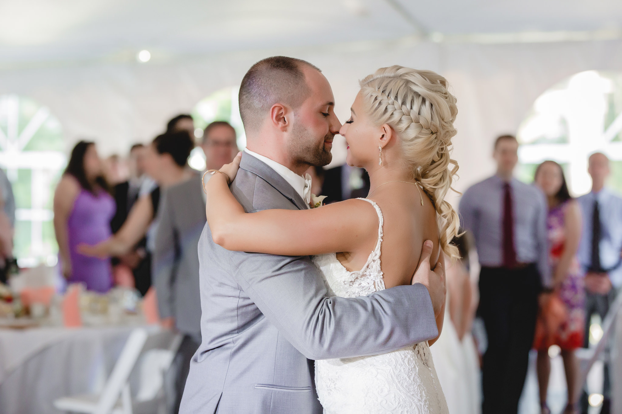 Bride and groom nuzzle noses during their first dance