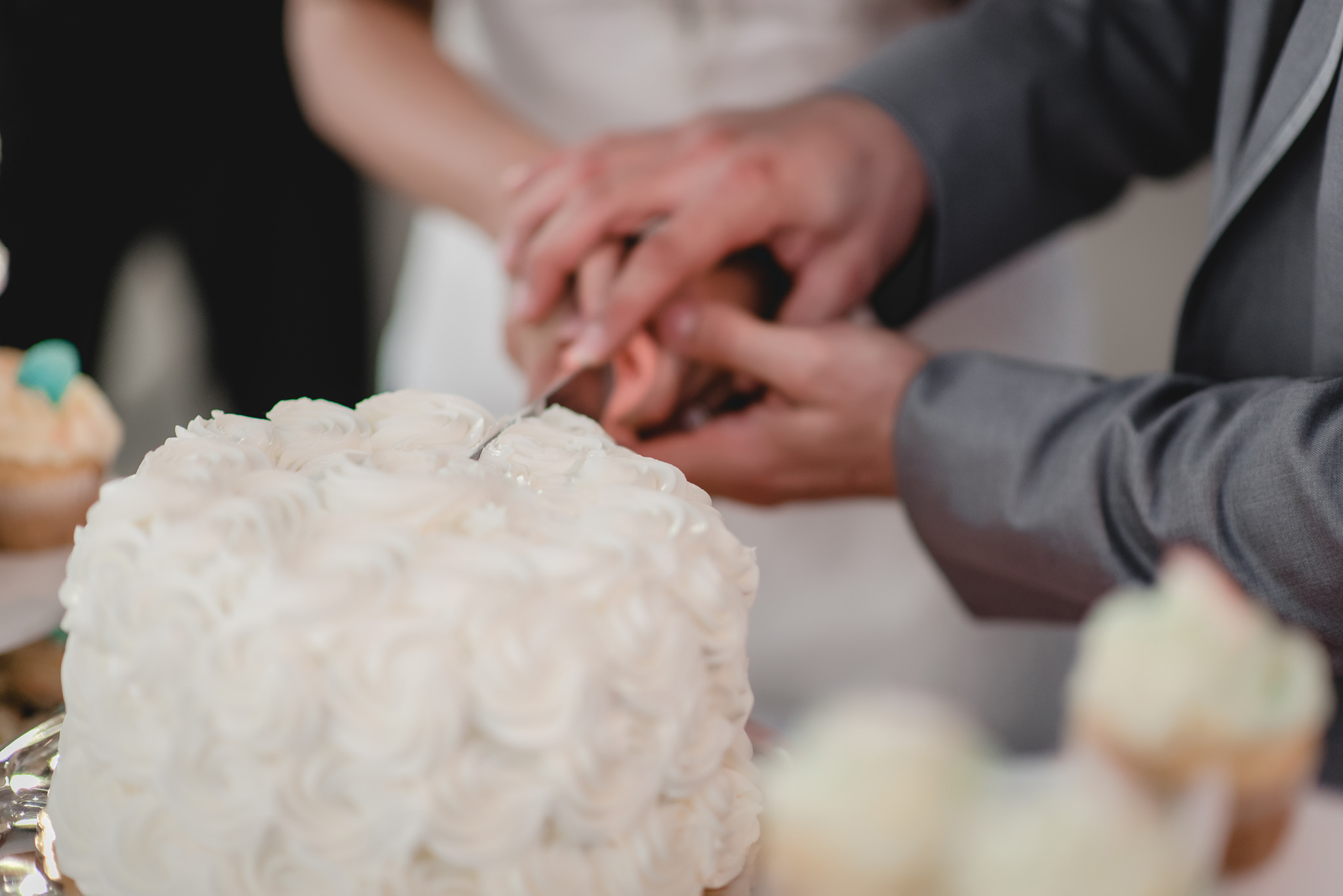 Closeup of bride and groom cutting their wedding cake