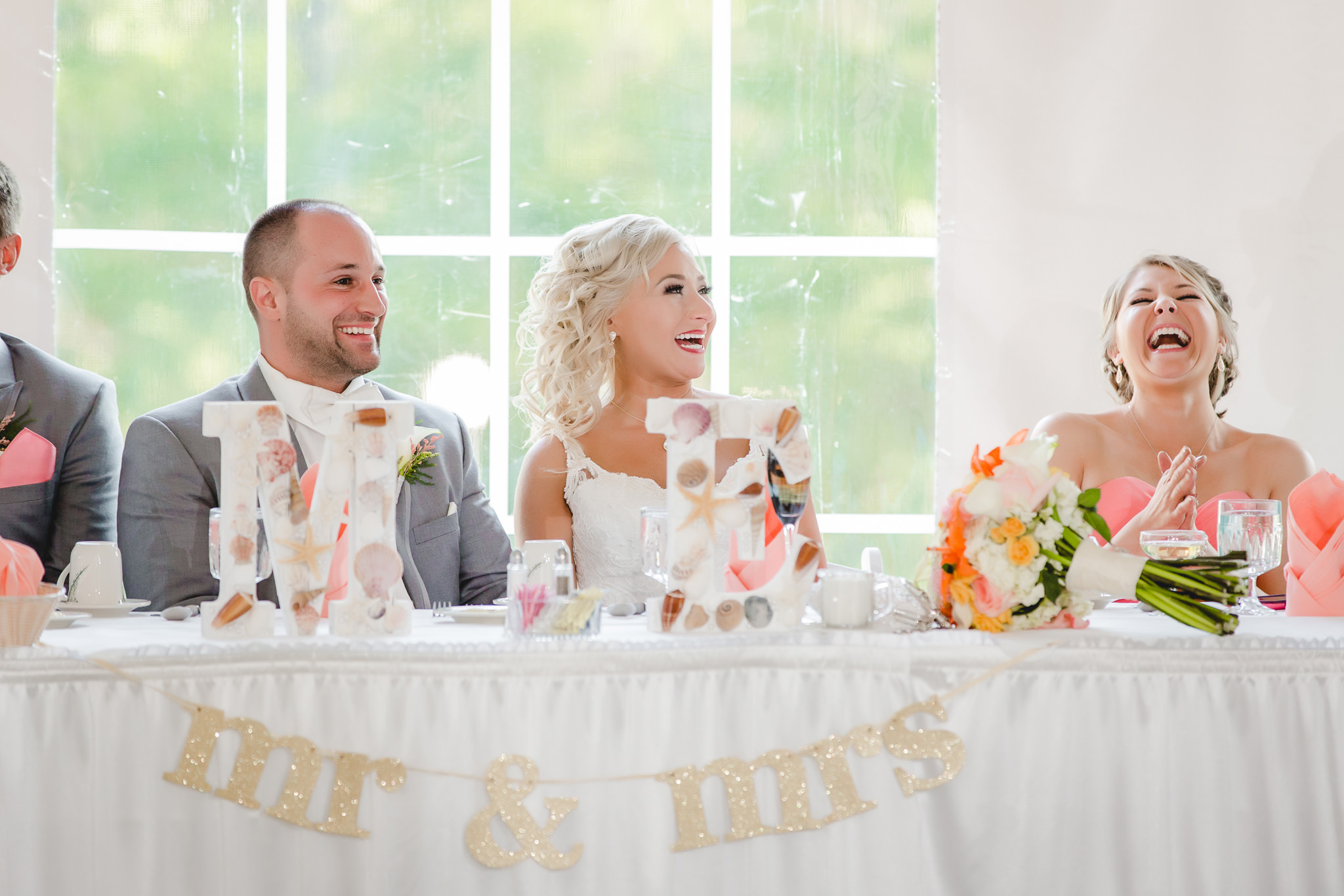 Bride and groom laugh during speeches at their reception