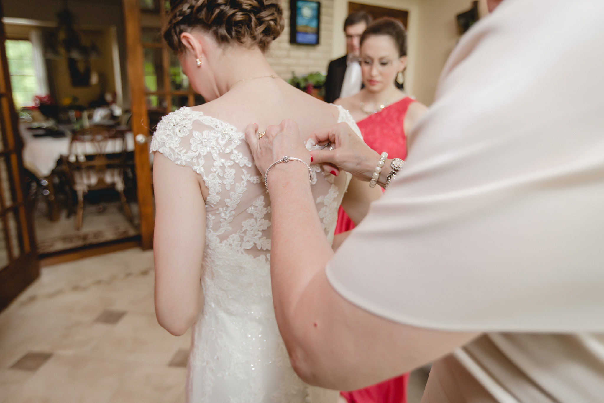 Bride's mother helps her into her dress before her Shannopin Country Club wedding