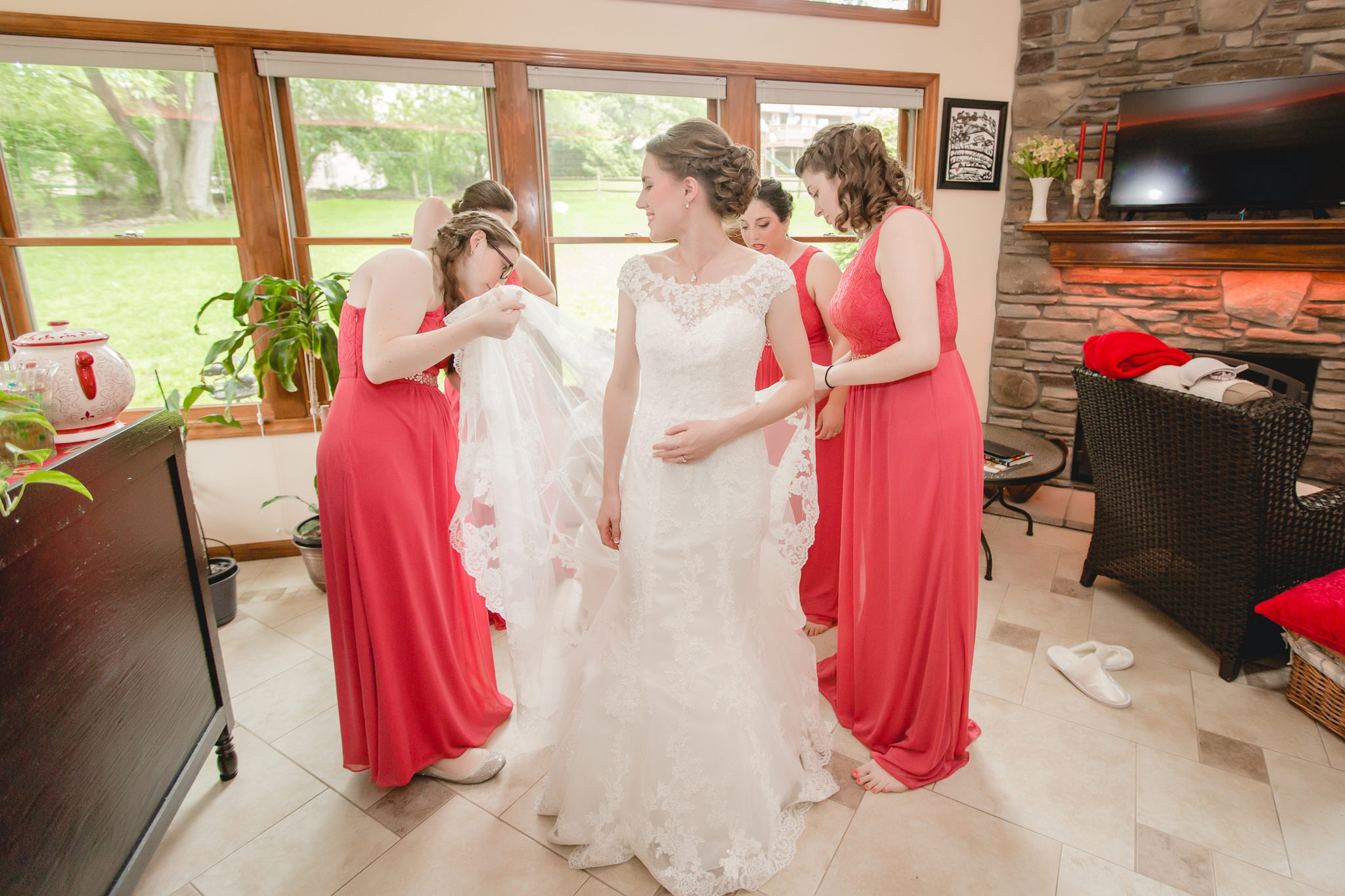 Bridesmaids help bride get dressed for her Shannopin Country Club wedding